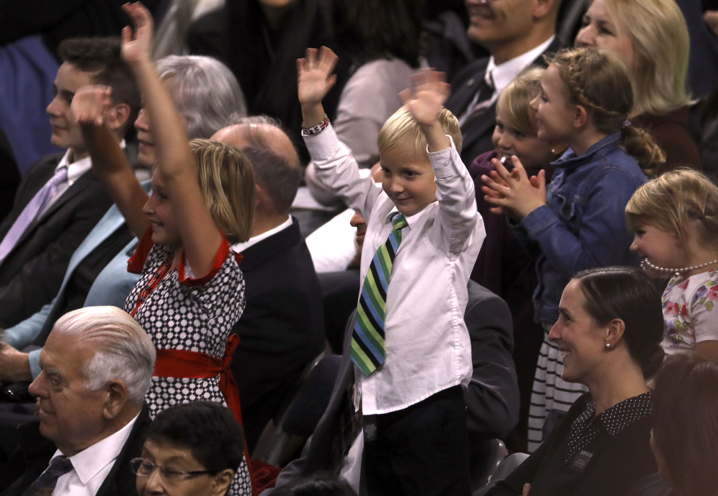 Primary children raise their hands at the request of President Russell M. Nelson during a devotional at the Langley Events Center in Langley, British Columbia, on Sunday, Sept. 16, 2018.