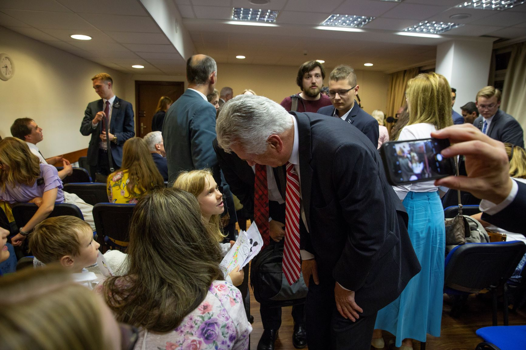 Elder Dieter F. Uchtdorf of the Quorum of the Twelve Apostles leans down to visit with children of the Gdansk Branch after his meeting with members and missionaries there on Sept. 17, 2018.