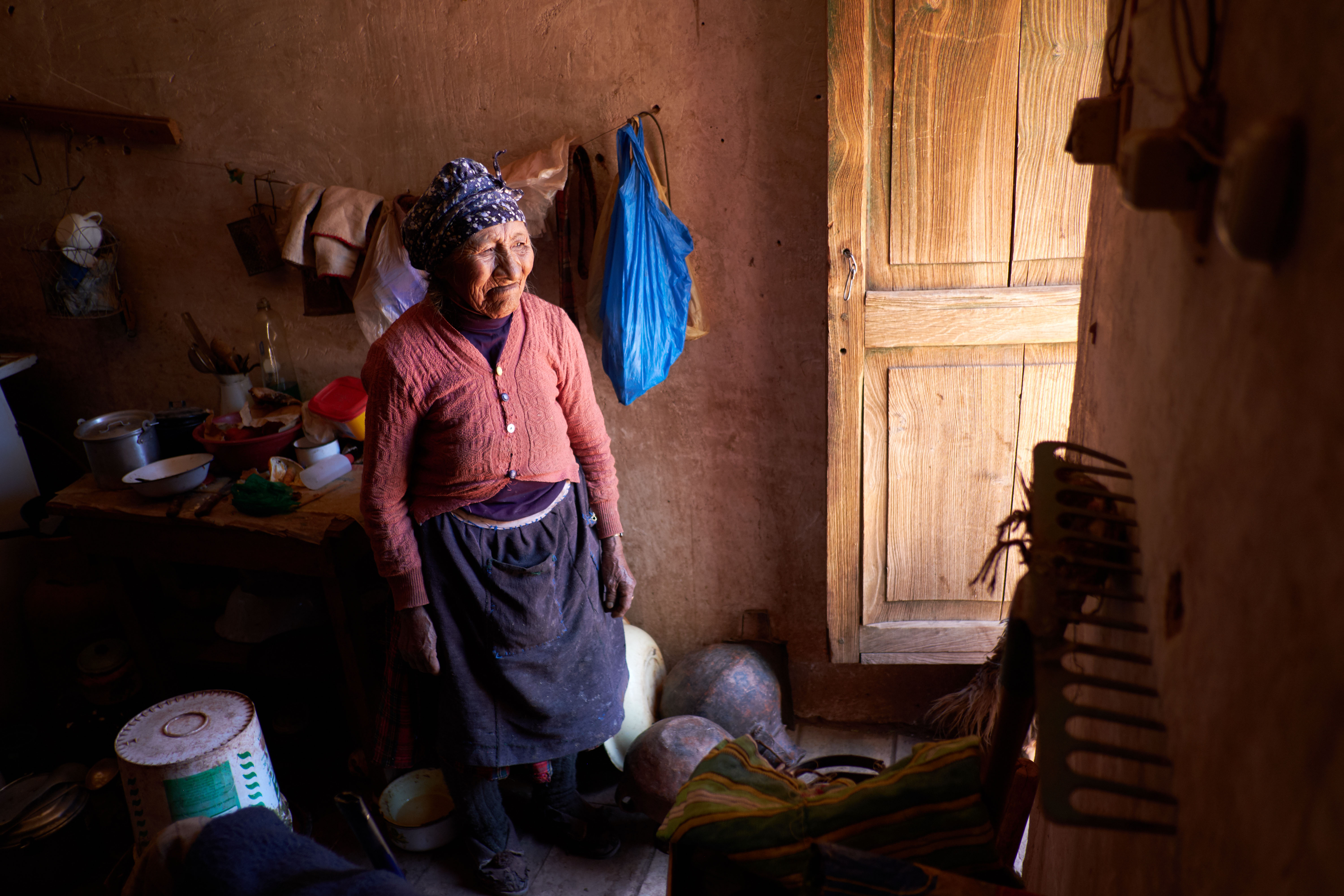 An elderly woman in Bolivia looks out her door. In 2018, LDS Charities responded to severe winter storms, flooding and mudslides in Bolivia.