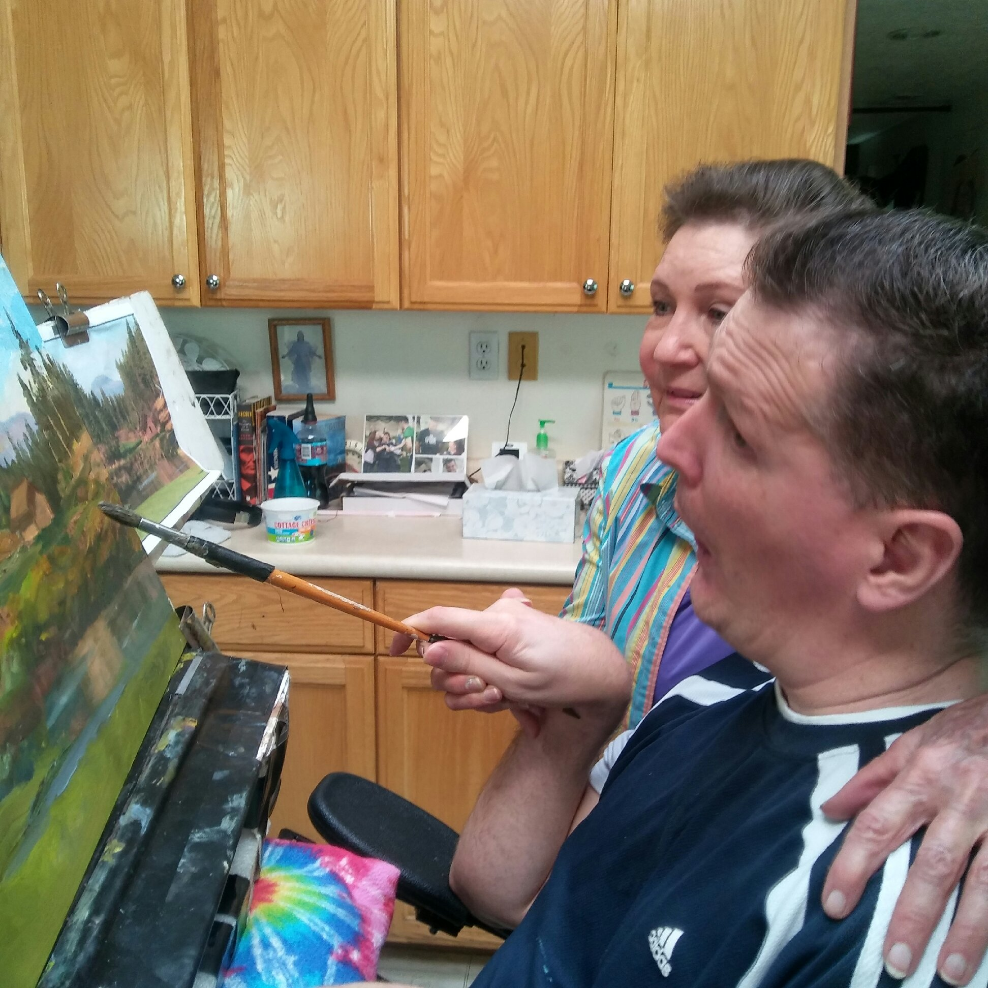 Orin Voorheis paints with his art teacher and friend, Carol Harding. More than 20 years after being shot in the head on his mission, Voorheis is living a happy life surrounded by family and friends.