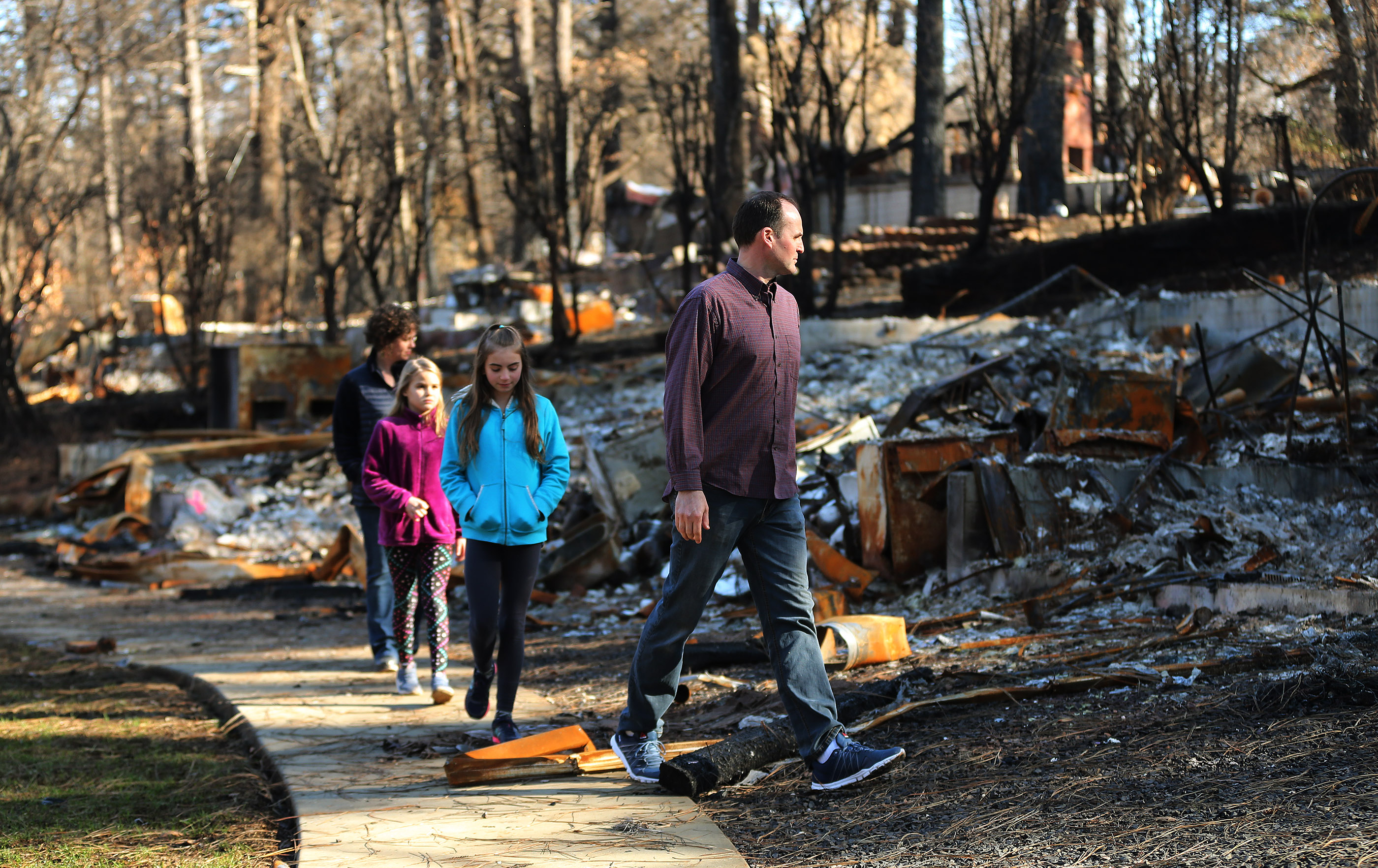 Jeremy and Brynn Chatfield and their children survey their destroyed home in Paradise, California, on Saturday, Jan. 12, 2019, two months after the Camp Fire destroyed more than 18,000 homes and businesses.