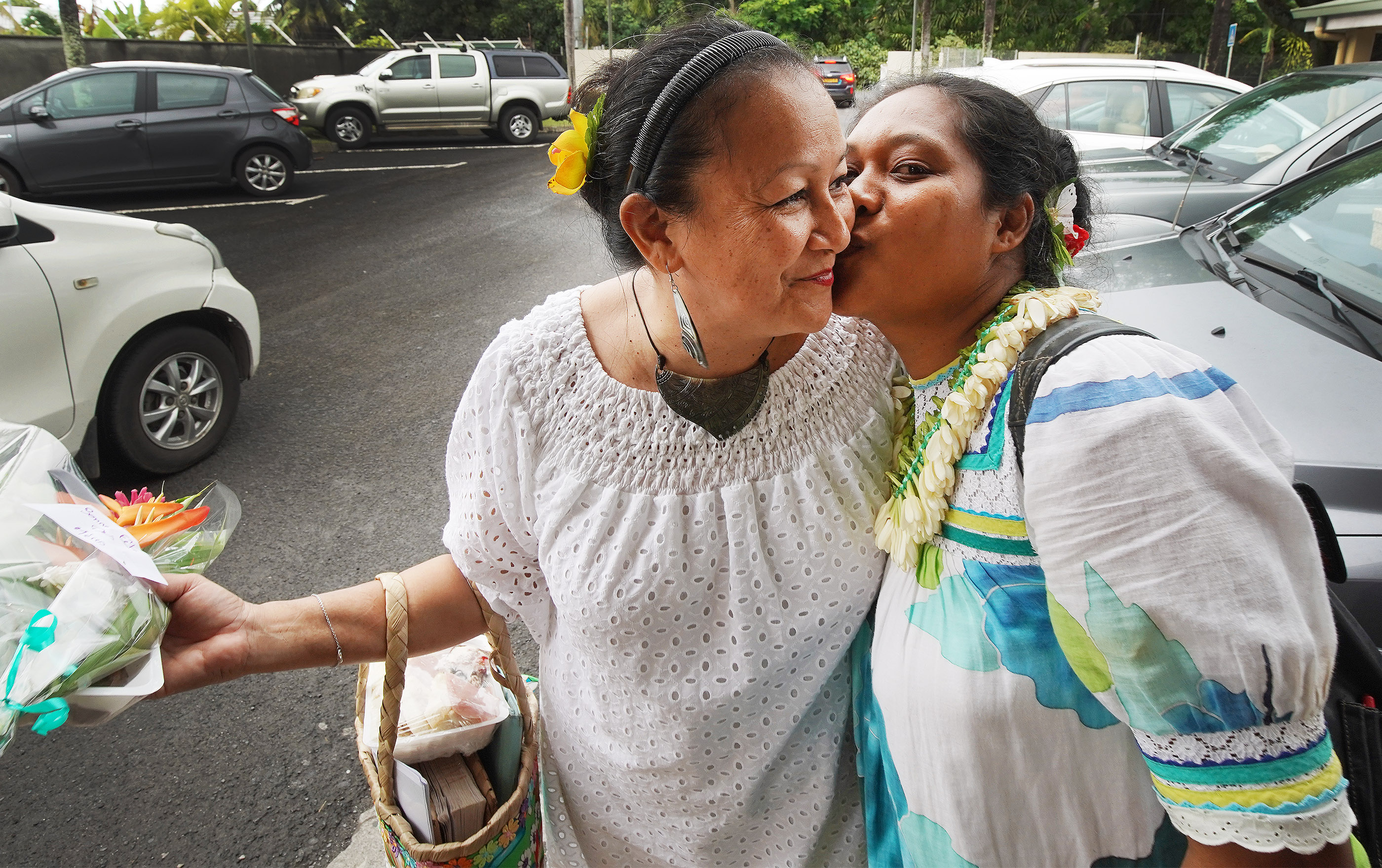 Voahina Alvarez gets a kiss and a flower for Mother's Day from Mataunui Vasthi at The Church of Jesus Christ of Latter-day Saints in Papeete, Tahiti, on May 26, 2019.