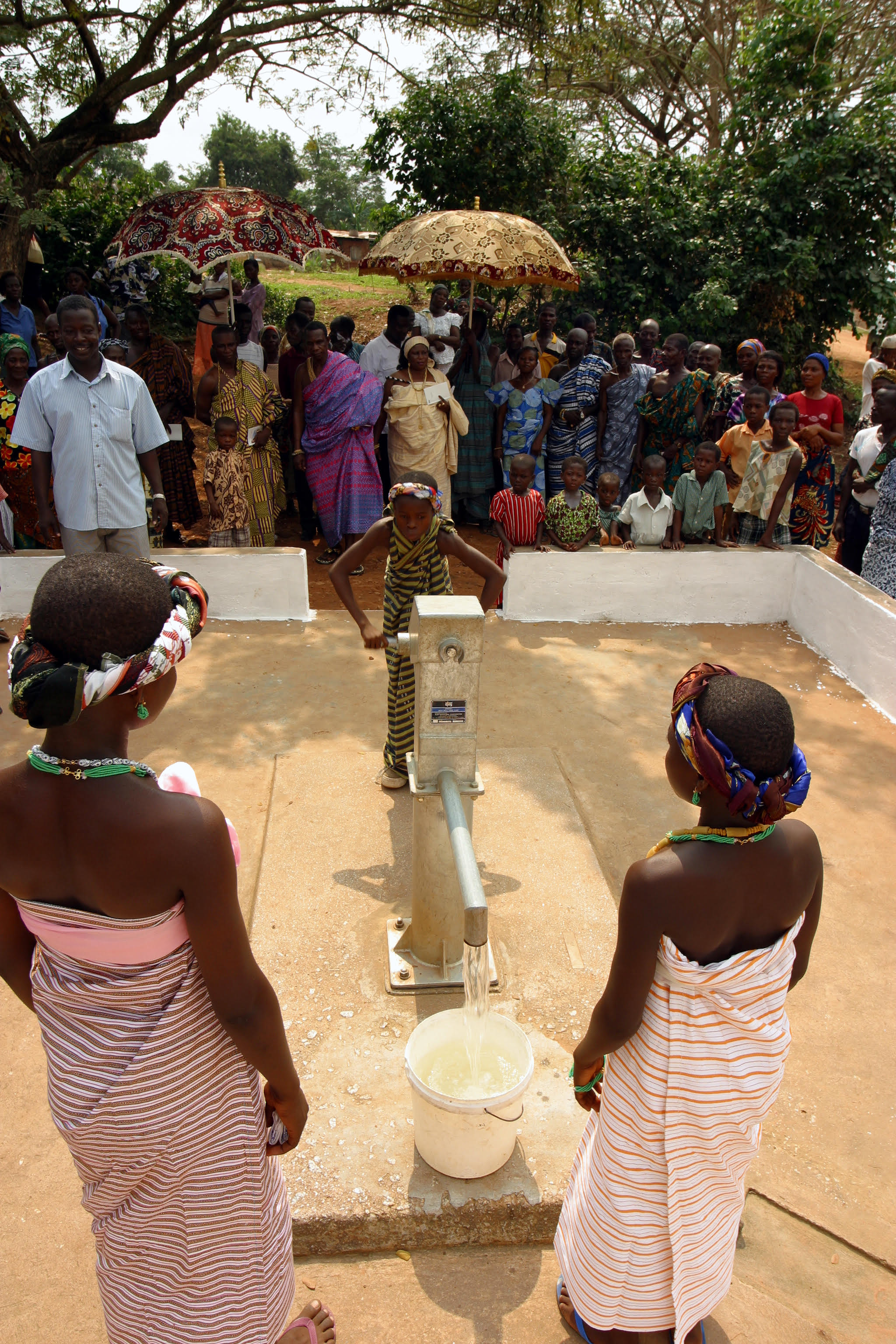 At a ceremony on Jan. 8, 2004, in which Latter-day Saint Charities handed two boreholes (fresh water wells) over to Ghana's village of Katapor, a young girl works the hand pump to start the flow of water into a bucket. Two other girls wait to present the water to village and district dignitaries.