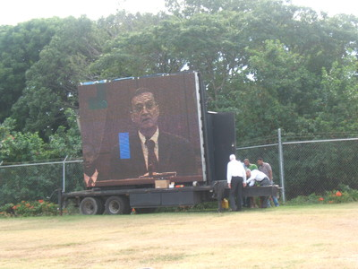 The large screen used for those seated in the overflow tent outside the Spanish Town meetinghouse to watch the conference proceedings.