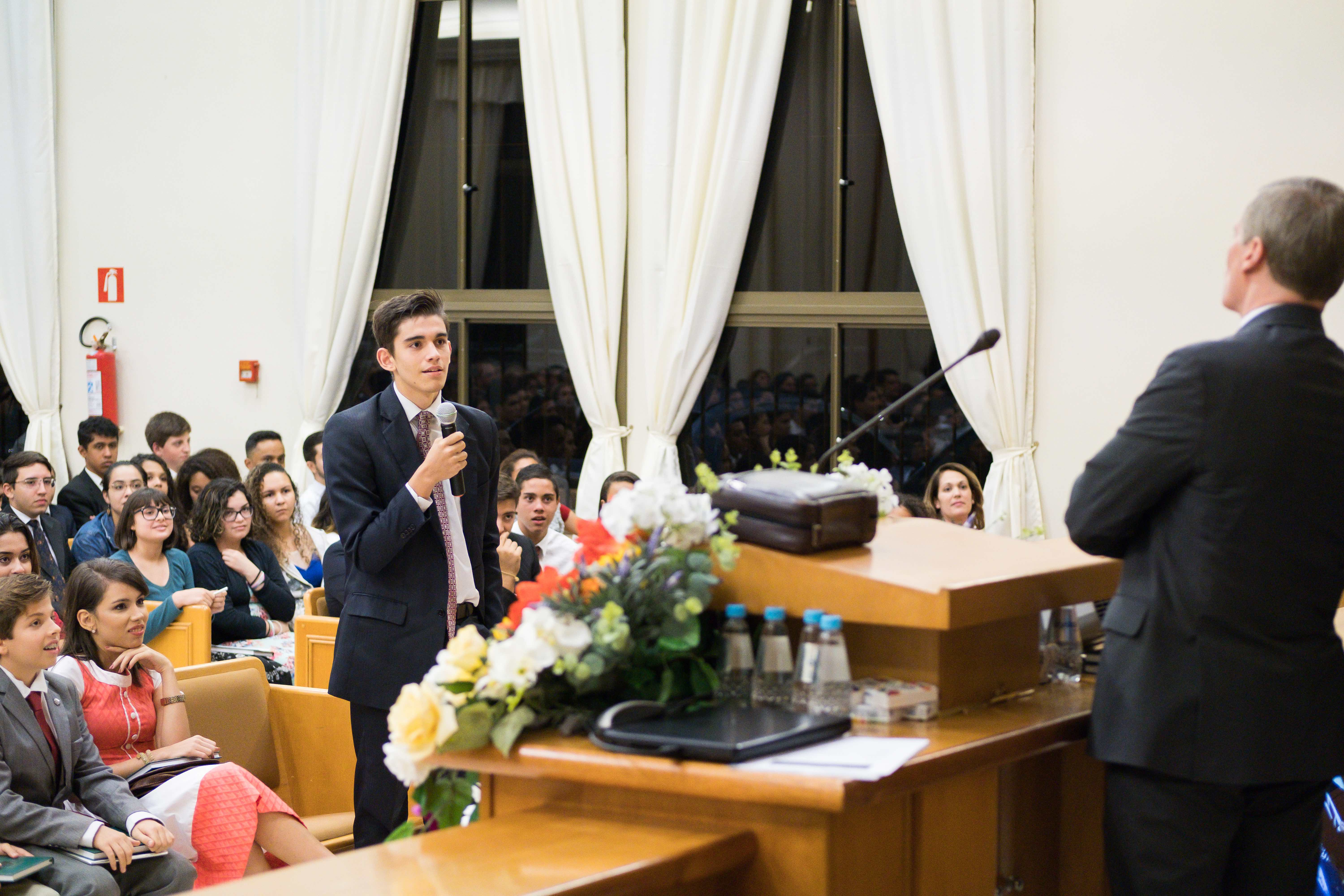 Young man in Sao Paulo asks Elder David A. Bednar of the Quorum of the Twelve Apostles a question during a youth meeting.