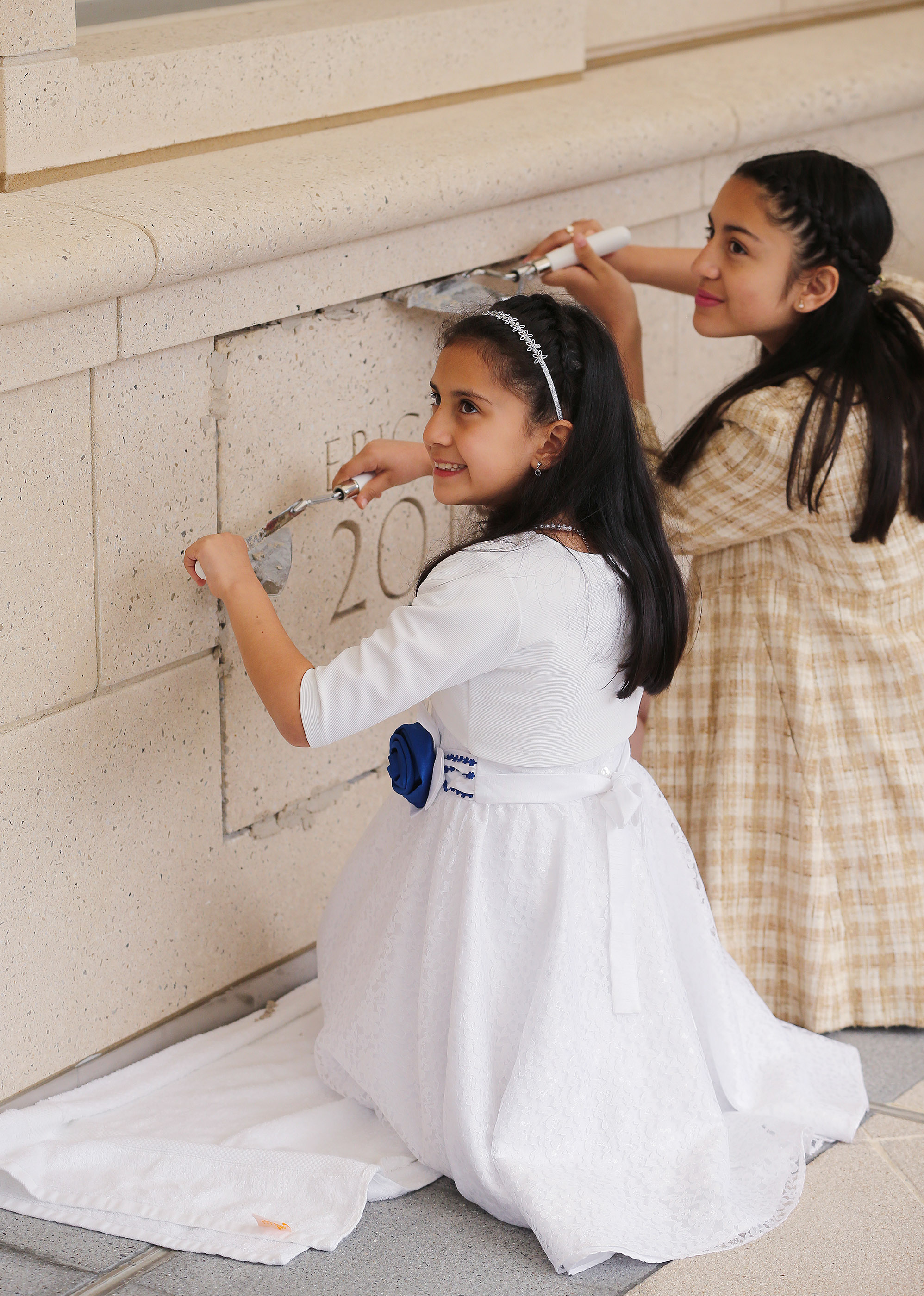 Laura and Alicia Ovalle place mortar in the cornerstone of the Concepcion Chile Temple on Sunday, Oct. 28, 2018, in Concepcion, Chile.