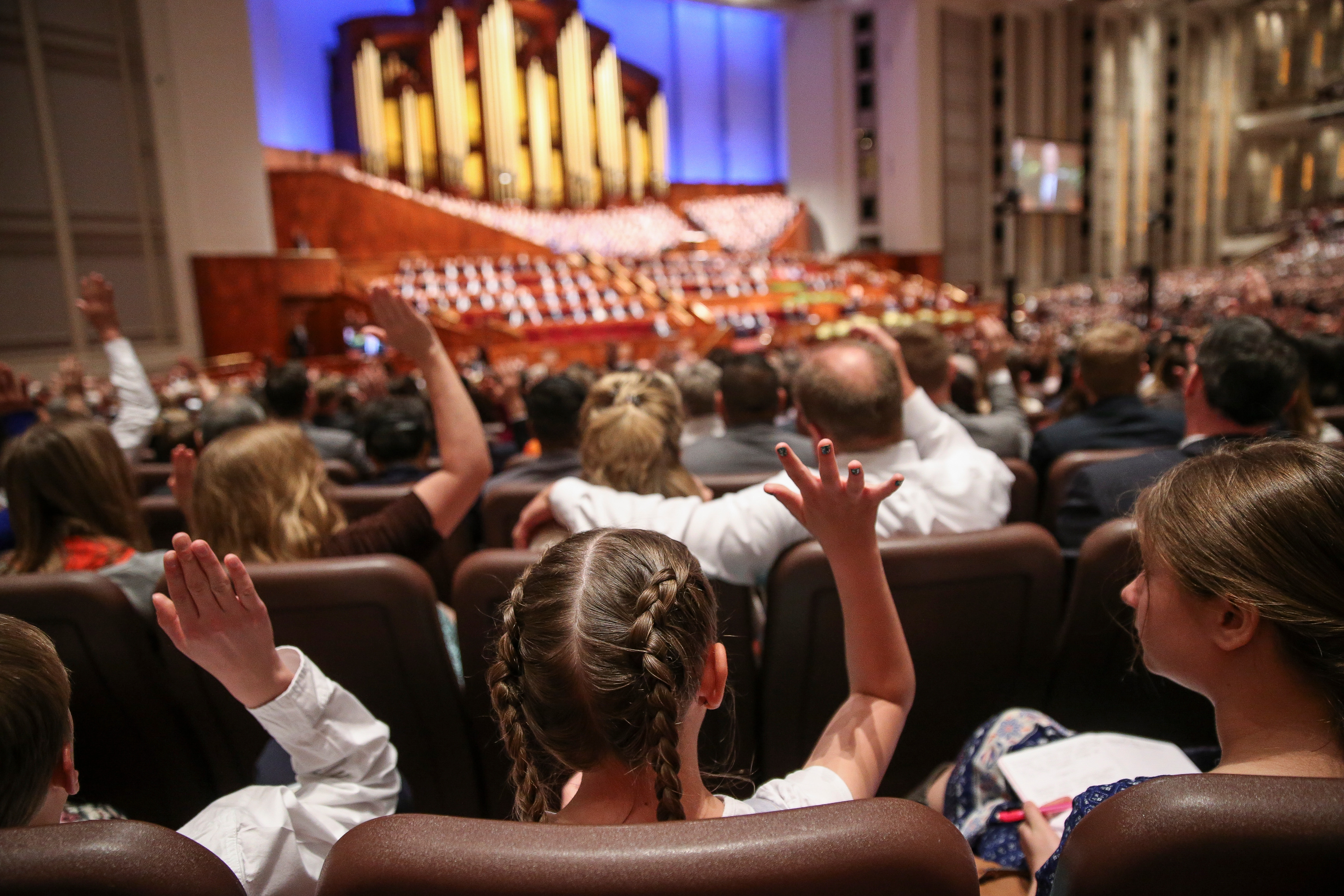 Young conferencegoers raise their hands to sustain church leadership during the Saturday afternoon session of the 188th Annual General Conference of the Church at the Conference Center in Salt Lake City on March 31, 2018.