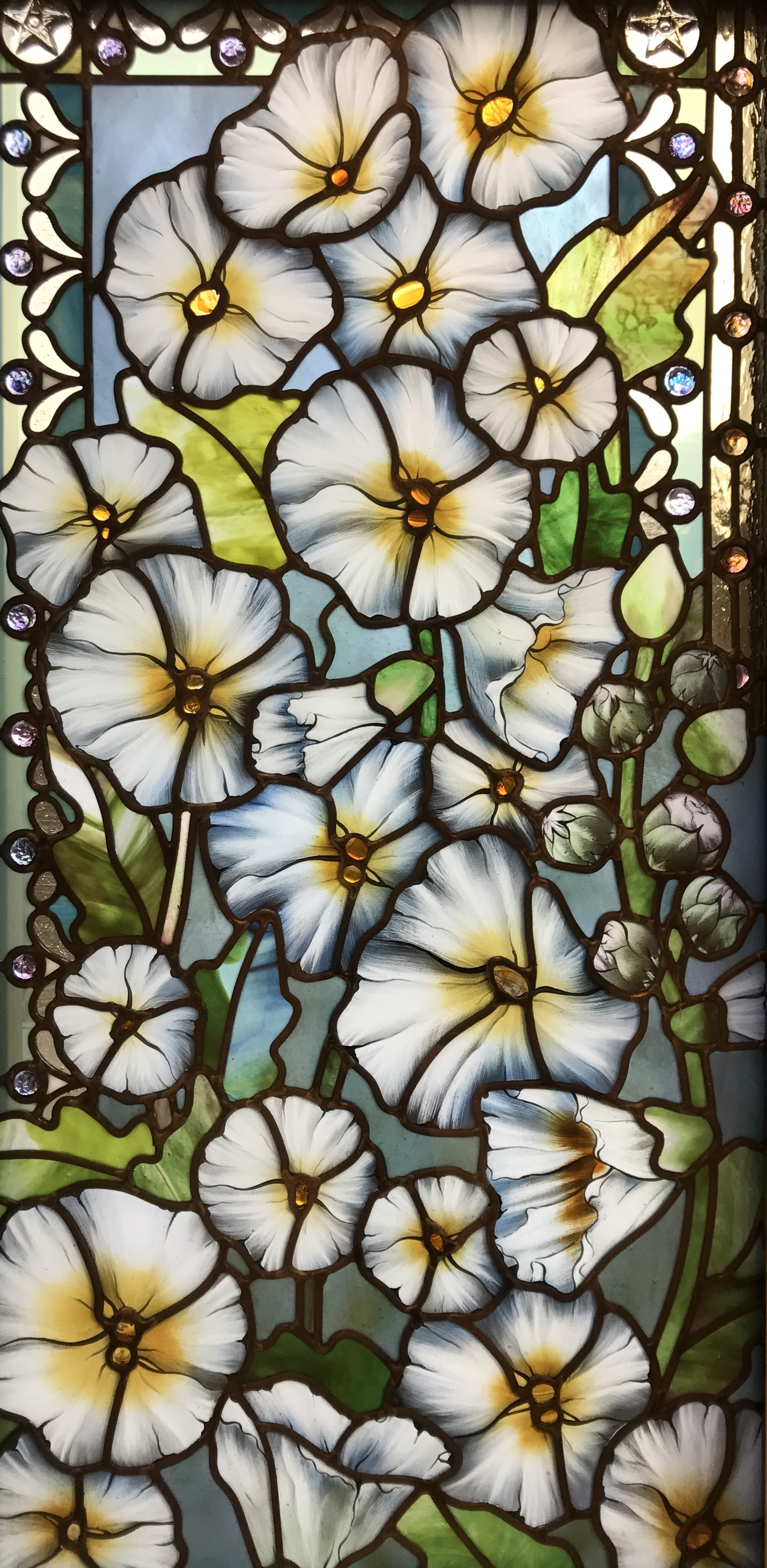 A window in the Celestial room Paris France. The celestial room windows feature white hollyhocks and custom made glass jewels from Holdman Studios.