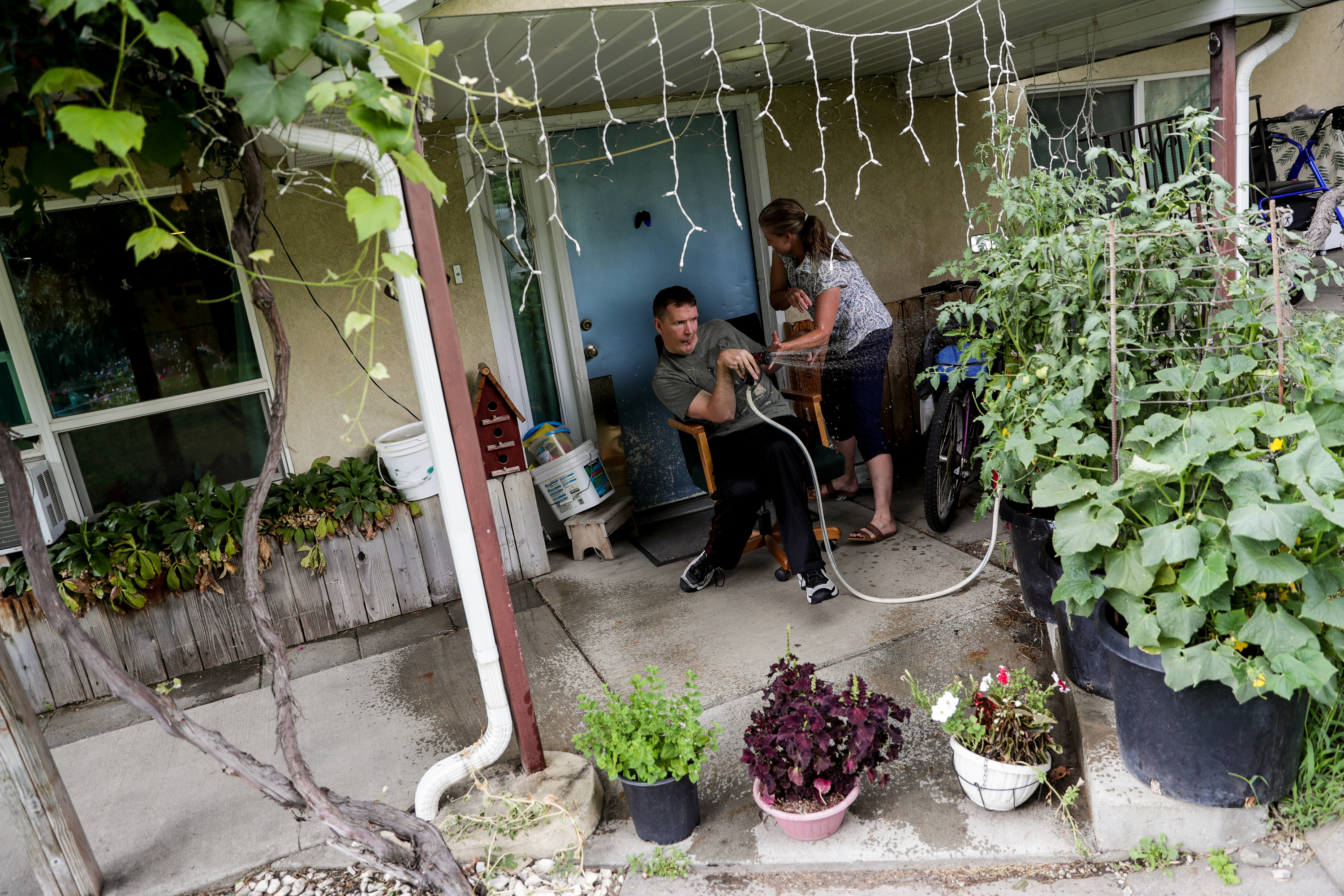 Orin Voorheis jokingly directs a hose at his caregiver, Wendy Tobey, while watering plants outside his home in Pleasant Grove, Utah, on Tuesday, July 10, 2018.