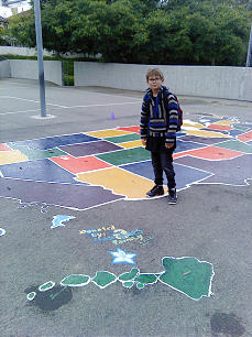 Chase Hales, on his first day of school, poses near the United States map his family restored at Marblehead Elementary, in San Clemente, Calif.