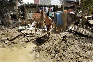 A Filipino man removes mud out of his home in Rizal province, east of Manila, Philippines on Sunday, Aug. 12, 2012.