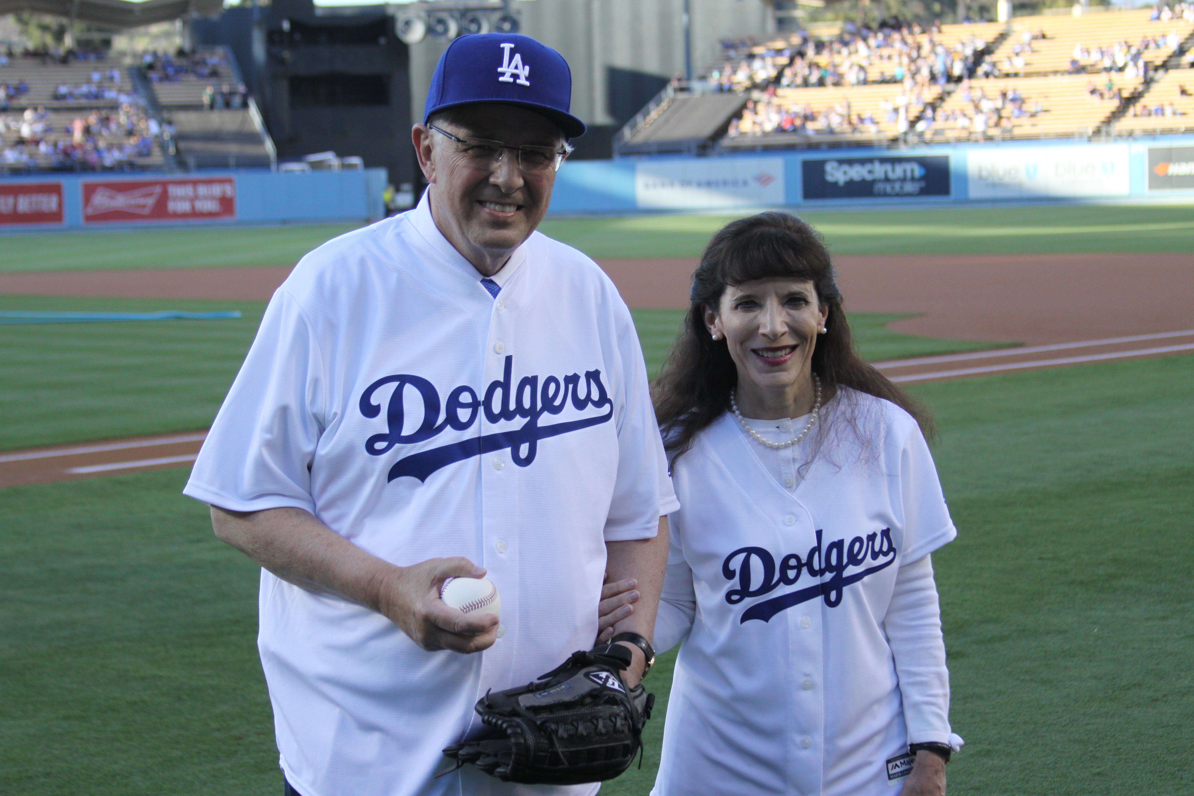 Elder Neil L. Andersen and his wife, Sister Kathy Andersen, on the field after Elder Andersen threw the first pitch at Dodger Stadium on July 19, 2019.