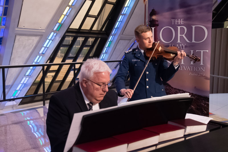 """Brother John M. Stoffey, LDS Cadet Choir accompanist and violinist, Jonah Angus (C2C) join the choir in a stirring rendition of """"Come, Thou Fount of Every Blessing."""""""