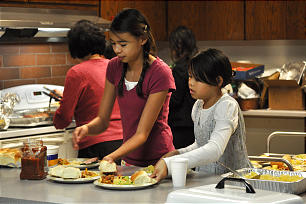 Ester Yuen, left, and Audrey Yuen help prepare dinner for the Christmas social of the new Yale Chinese-speaking Branch.