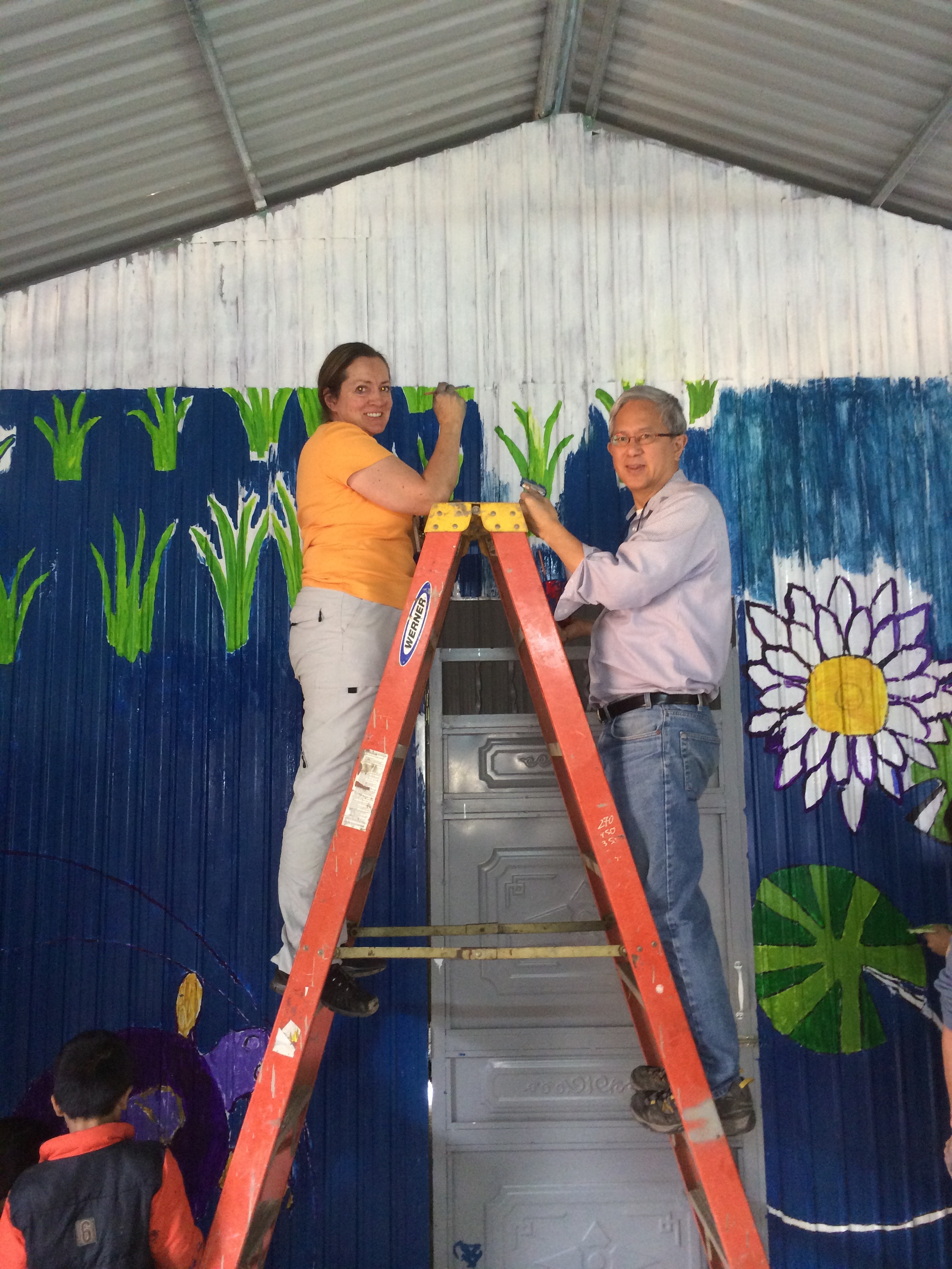 Elder Gerrit W. Gong and his wife, Susan, participate in a Christmas Mural project in Vietnam.