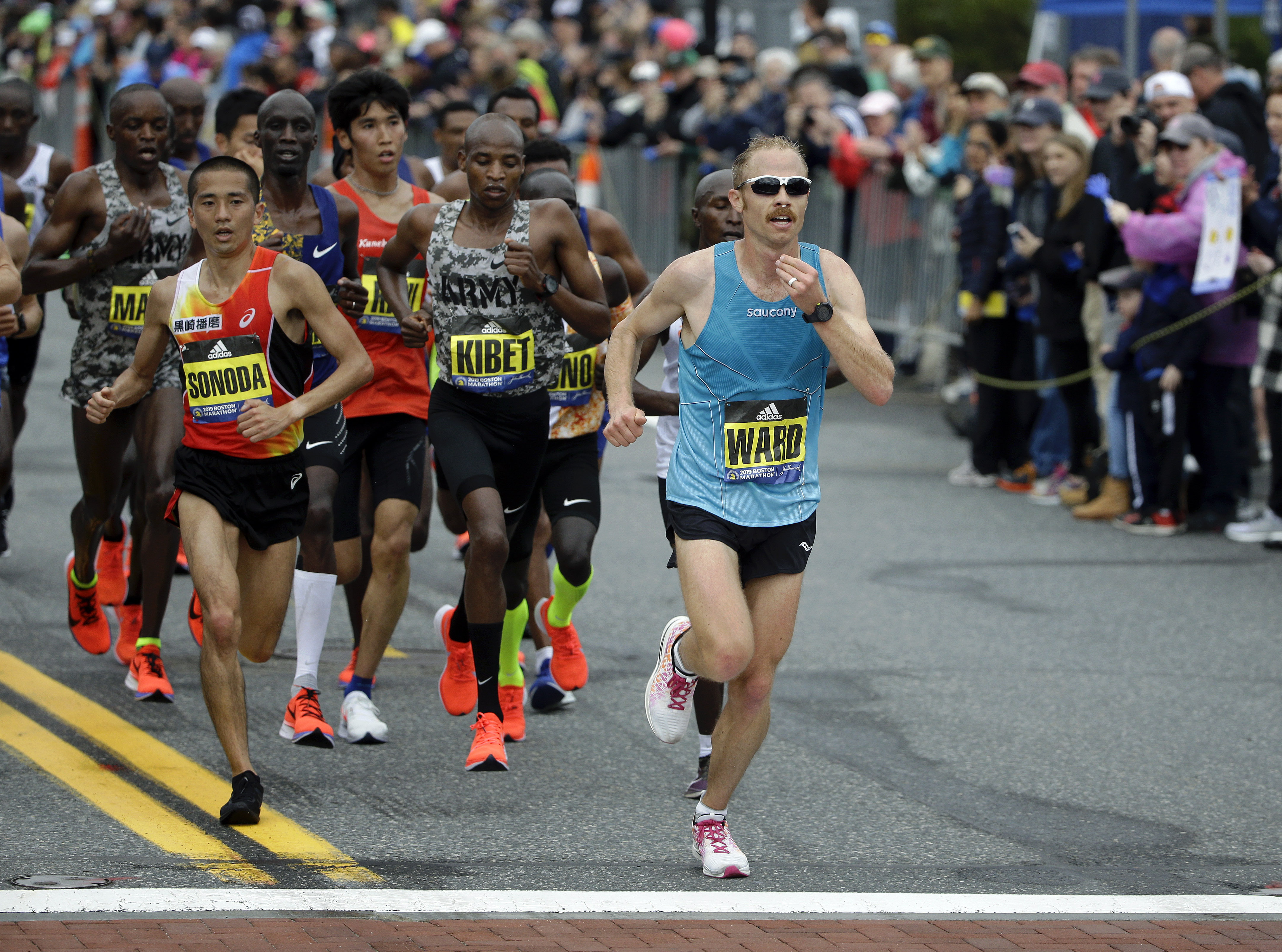 Jared Ward, of Mapleton, Utah, right, leads the pack ahead of Hayato Sonoda, left, of Japan, and Elkanah Kibet, center, of Fountain, Colo., as they run the course during the 123rd Boston Marathon on Monday, April 15, 2019, in Boston. (AP Photo/Steven Senne)