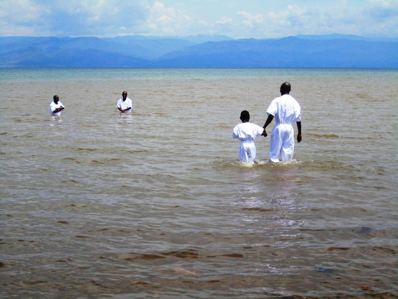 On Oct. 23, just a few weeks after the LDS Church's branch in Uvira, Democratic Republic of the Congo, Africa, was established, the first baptismal service in the actual city of Uvira was in the nearby waters of Lake Tanganyika. The newly called branch president walks with his young son to perform to where the witnesses are for the baptism.