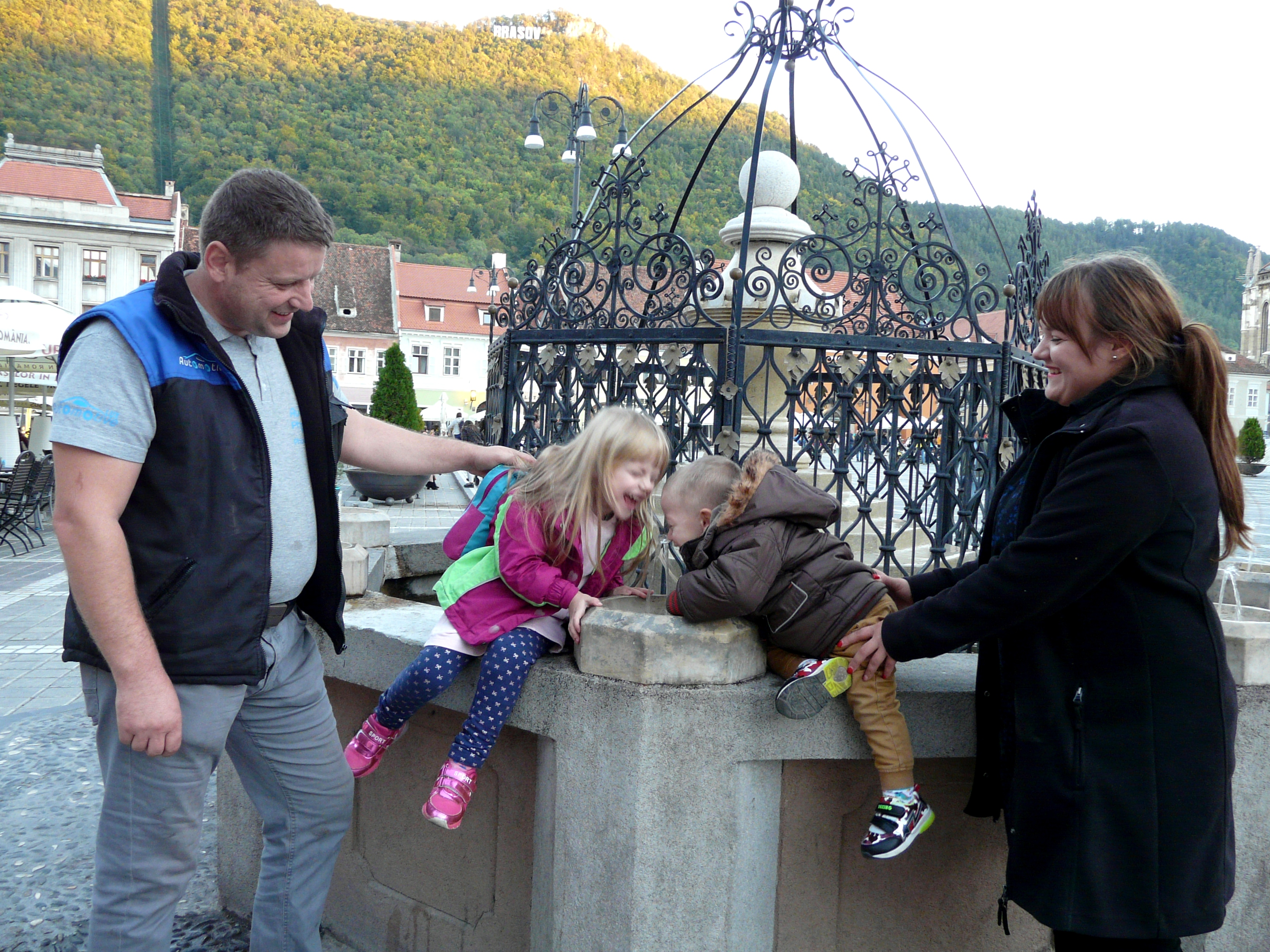 The Mesco family enjoys a fountain in the historic main square of Brasov. The South Carpathian mountains surround the town.