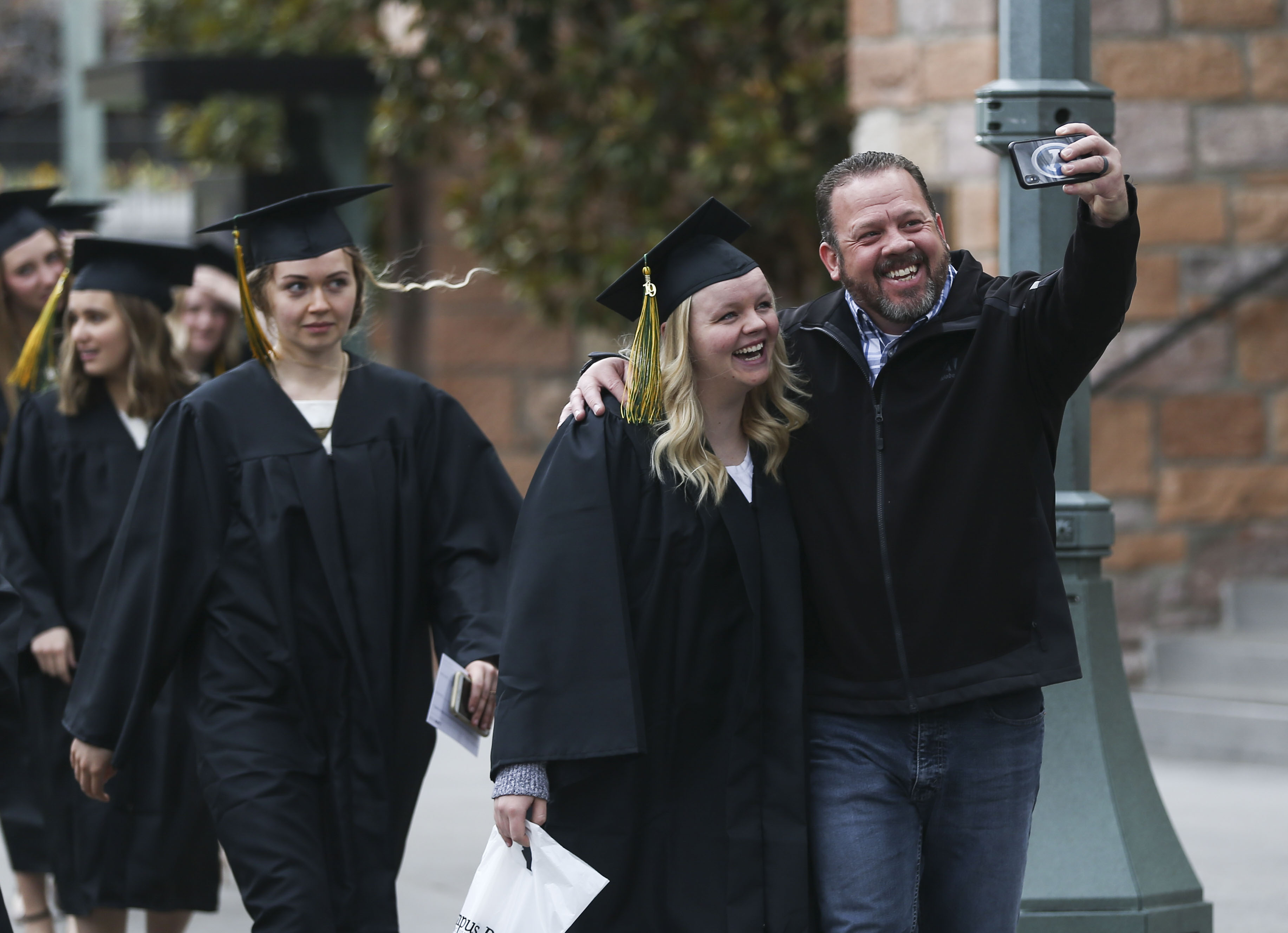 LDS business college graduate takes a selfie with her father while walking to the Tabernacle on Temple Square for her commencement ceremony in Salt Lake City on Friday, April 12, 2019.