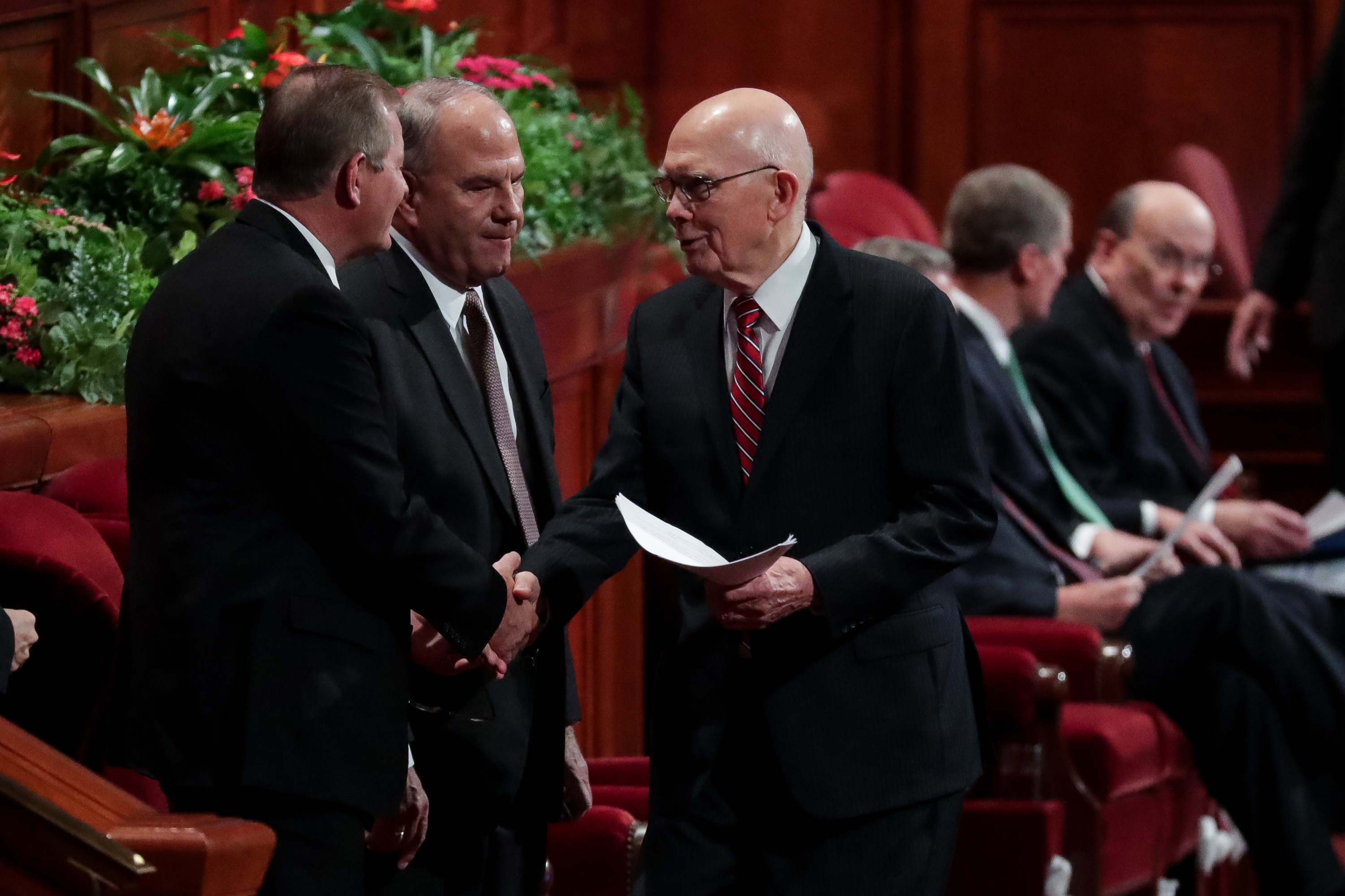 President Dallin H. Oaks, first counselor in the First Presidency, greets Elder Gary E. Stevenson, left, and Elder Ronald A. Rasband, center, both of the Quorum of the Twelve Apostles, before the start of the Saturday morning session of the 188th Semiannual General Conference of The Church of Jesus Christ of Latter-day Saints in the Conference Center in Salt Lake City on Saturday, Oct. 6, 2018.