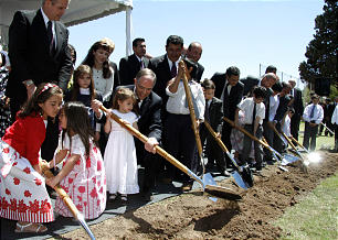 Elder Neil L. Andersen of the Quorum of the Twelve assists a child during groundbreaking ceremony in Cordoba, Argentina.