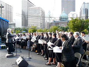 A choir directed by Linda Davenport sings at the groundbreaking of the Philadelphia Temple under cloudy but rainless skies.