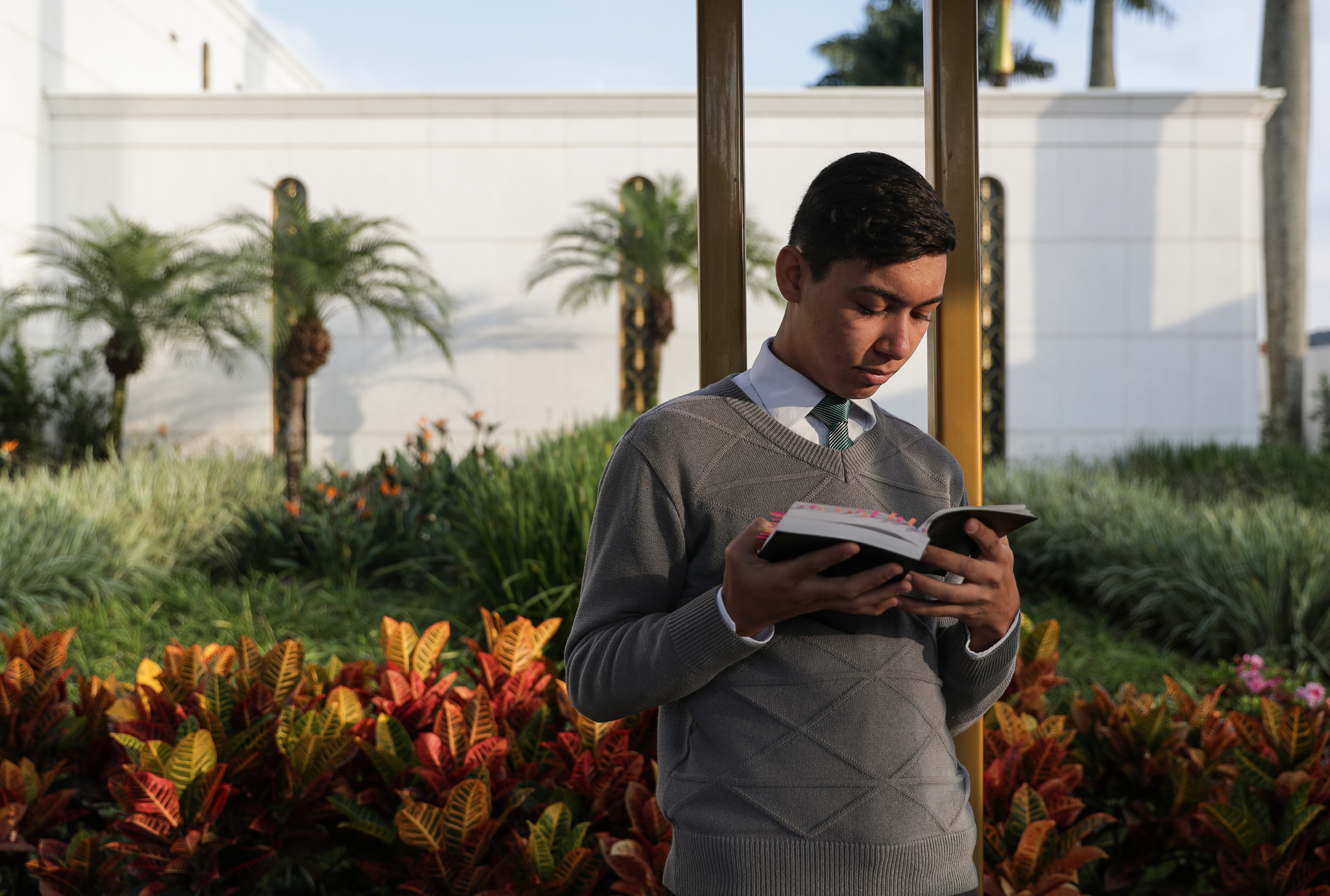 Marcos Silva, 18, reads a copy of The Book of Mormon outside the LDS Church's São Paulo Temple before going to work for the day in the church's area offices in São Paulo, Brazil on Thursday, May 24, 2018.