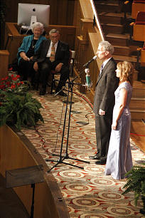 Tabernacle organist Richard Elliott, with guest soloist Andrea Paulsen, Tabernacle Choir member, at his side, introduces their portion of the recital to audience and Wanda and Melvin Palmer look from the side.