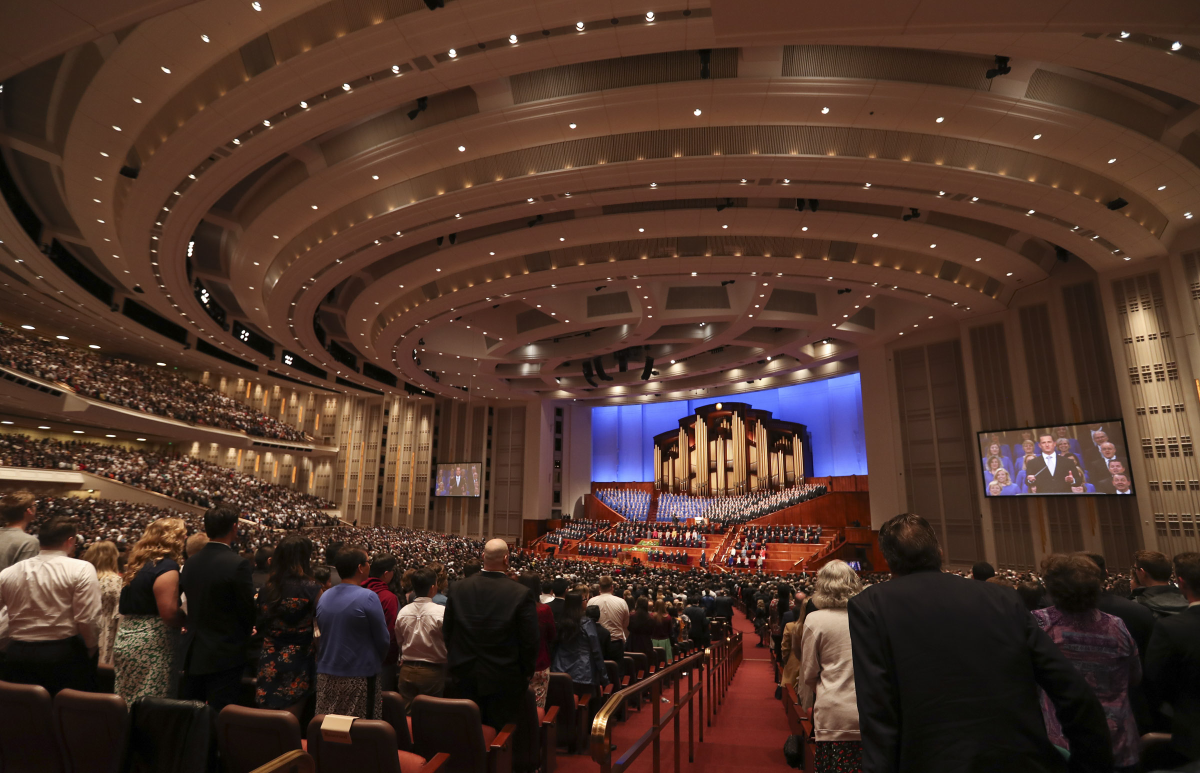 Latter-day Saints stand and sing with The Tabernacle Choir at Temple Square in the Conference Center in Salt Lake City during the morning session of the 189th Annual General Conference of The Church of Jesus Christ of Latter-day Saints on Saturday, April 6, 2019.