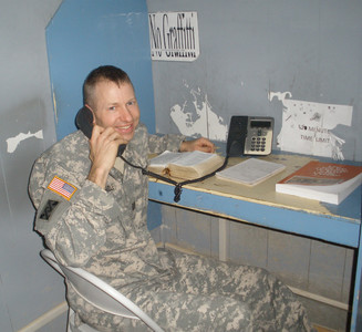 """Capt. Aaron Cheadle sets up his """"classroom"""" at a desk in Baghdad, Iraq, to teach a seminary lesson by telephone to his sons in rural Minneota, Minnesota, each school day morning. He felt inspired to take over of teaching home seminary from his wife, Laura, who is alone caring for their seven children."""
