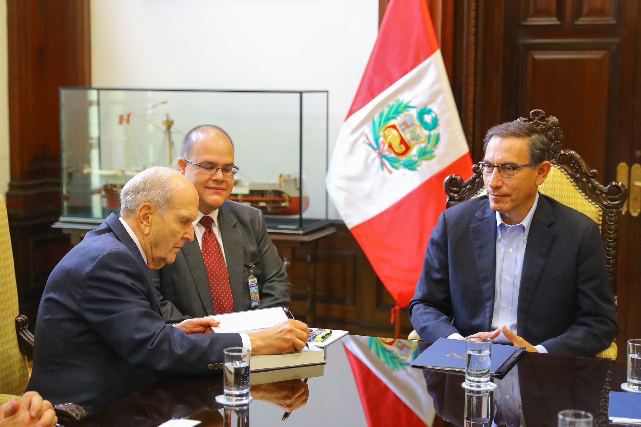 """President Russell M. Nelson signs his book, """"Teachings of President Russell M. Nelson,"""" which he presented to Peru's president, Martín Vizcarra, right, at the presidential palace in Lima, Peru, on Saturday, Oct. 20, 2018."""