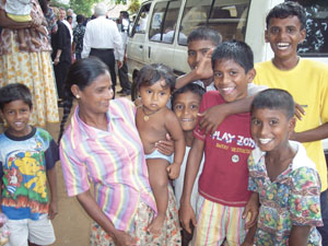 Families in Sri Lanka affected by tsunami gather around van for relief supplies being distributed by Church leaders.