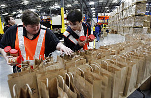Elder Jonathan Phan, left, and Elder Richard Selman prepare sacks of goods to be handed out during the dedication of the new 570,000 square foot Utah Bishops' Central Storehouse in Salt Lake City, Thursday, Jan. 26, 2012.