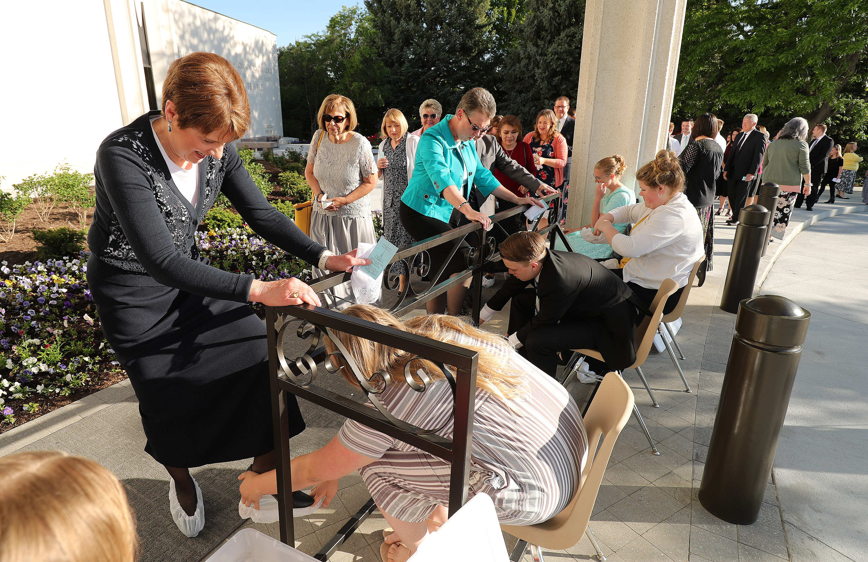 Attendees are booted as they arrive for the Jordan River Utah Temple rededication in South Jordan on Sunday, May 20, 2018.
