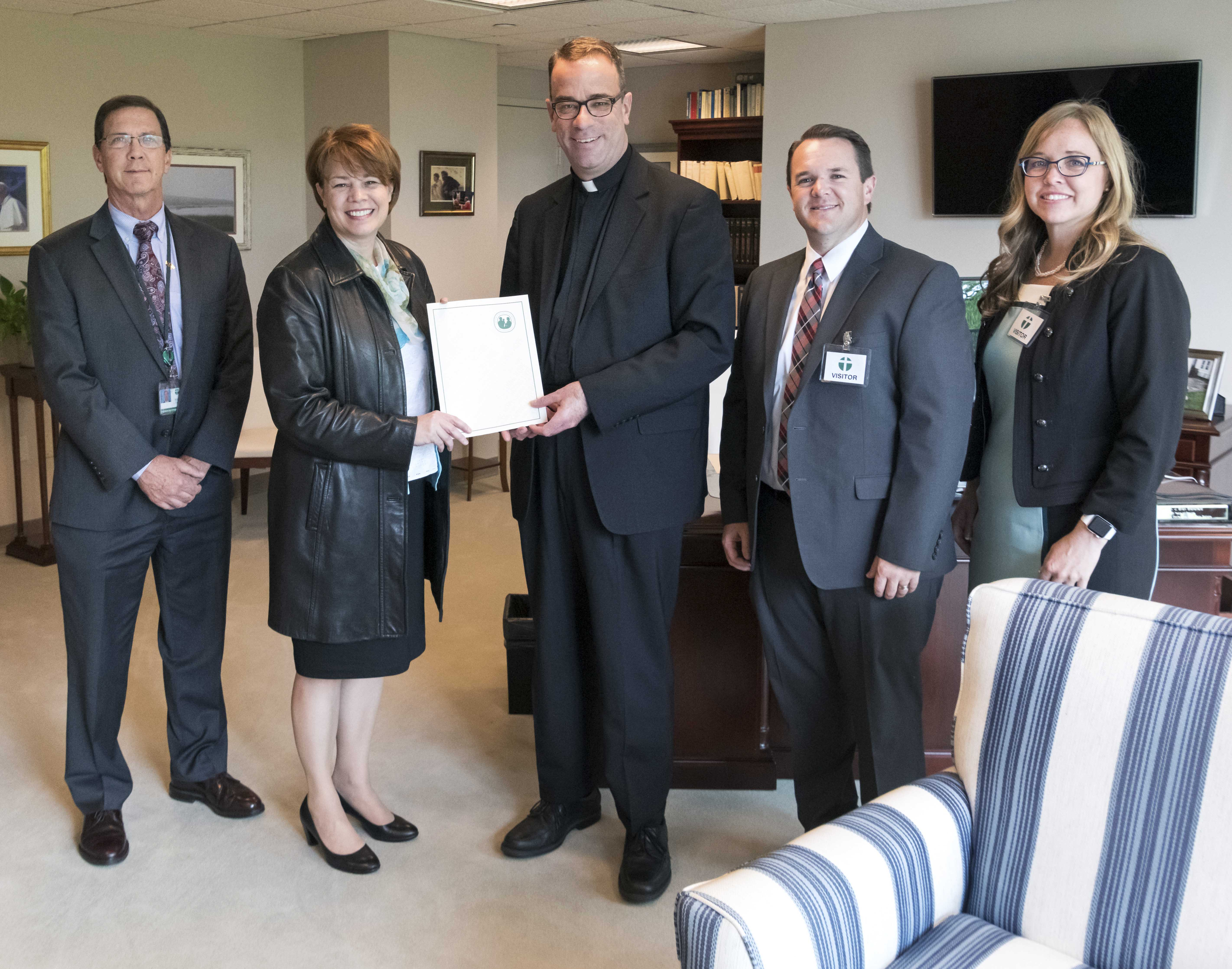 Sister Sharon Eubank, second from left, president of Latter-day Saint Charities, presents a grant from the Church to the Reverend Monsignor J. Brian Bransfield, center, general secretary of the United States Conference of Catholic Bishops (USCCB) May 14, 2019. Also present are William Canny, left, USCCB executive director; Shawn Johnson, second from right, director of the Church's Humanitarian Services; and Elissa McConkie, right, manager of Humanitarian Services Major Initiatives.
