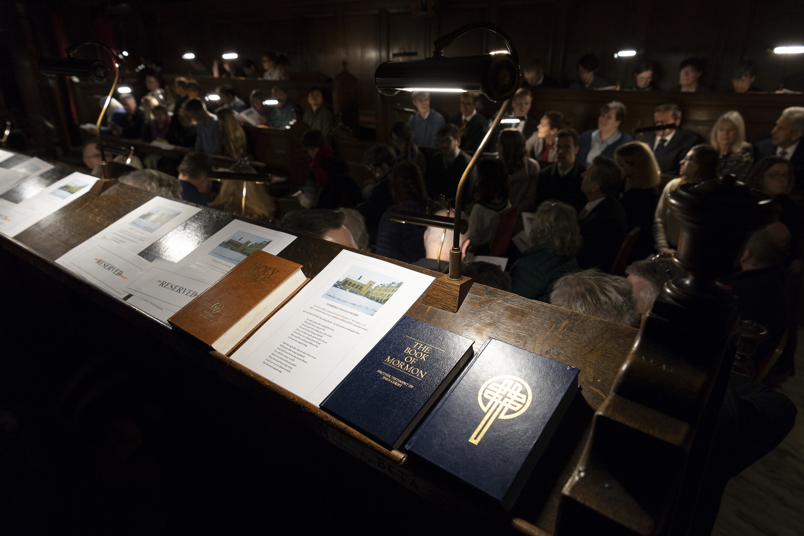 """A Bible, a Book of Mormon and a Church of England Lectionary of worship texts rest on a lectern on the top row of benches before start of the traditional Church of England """"Nine Lessons and Carols"""" service at the Pembroke College Chapel in Oxford, England, on Sunday, Nov. 25, 2018."""