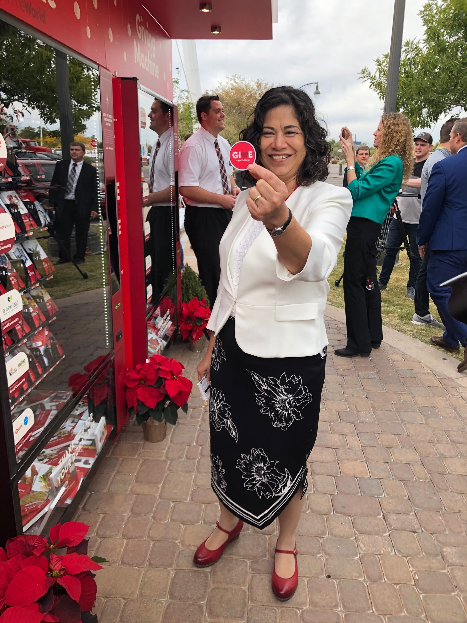 Sister Reyna Aburto, second counselor in the Relief Society general presidency, holds up her #LightTheWorld Give sticker in front of the Church's giving machines. Part of the Church's popular #LightTheWorld campaign, the machines opened in Gilbert, Arizona, on Thursday, Nov. 29.