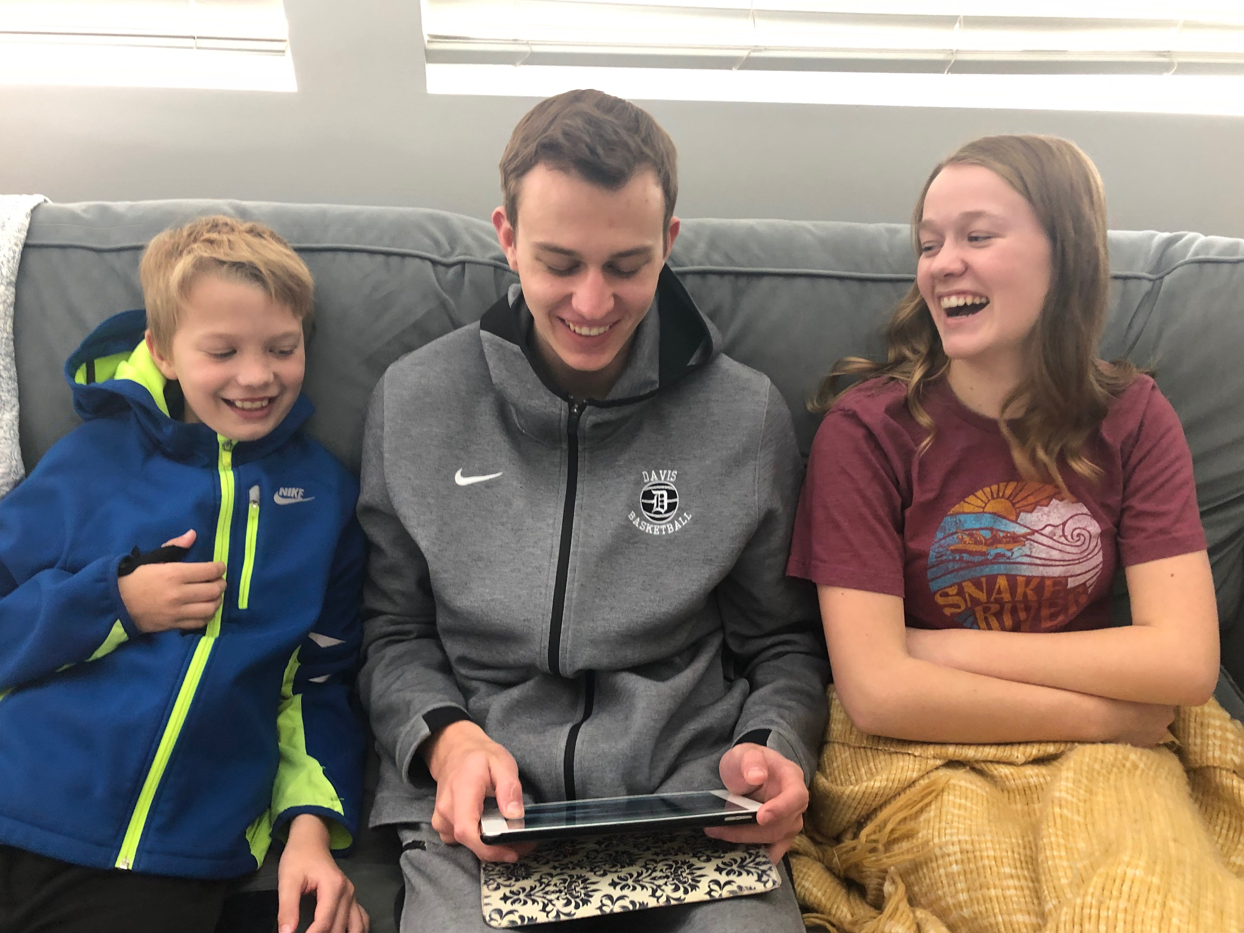 "Thomas, Sam, and Grace Arrington from Farmington, Utah, share a laugh while using the ""Walk Where They Walked"" in-home activity on FamilySearch."