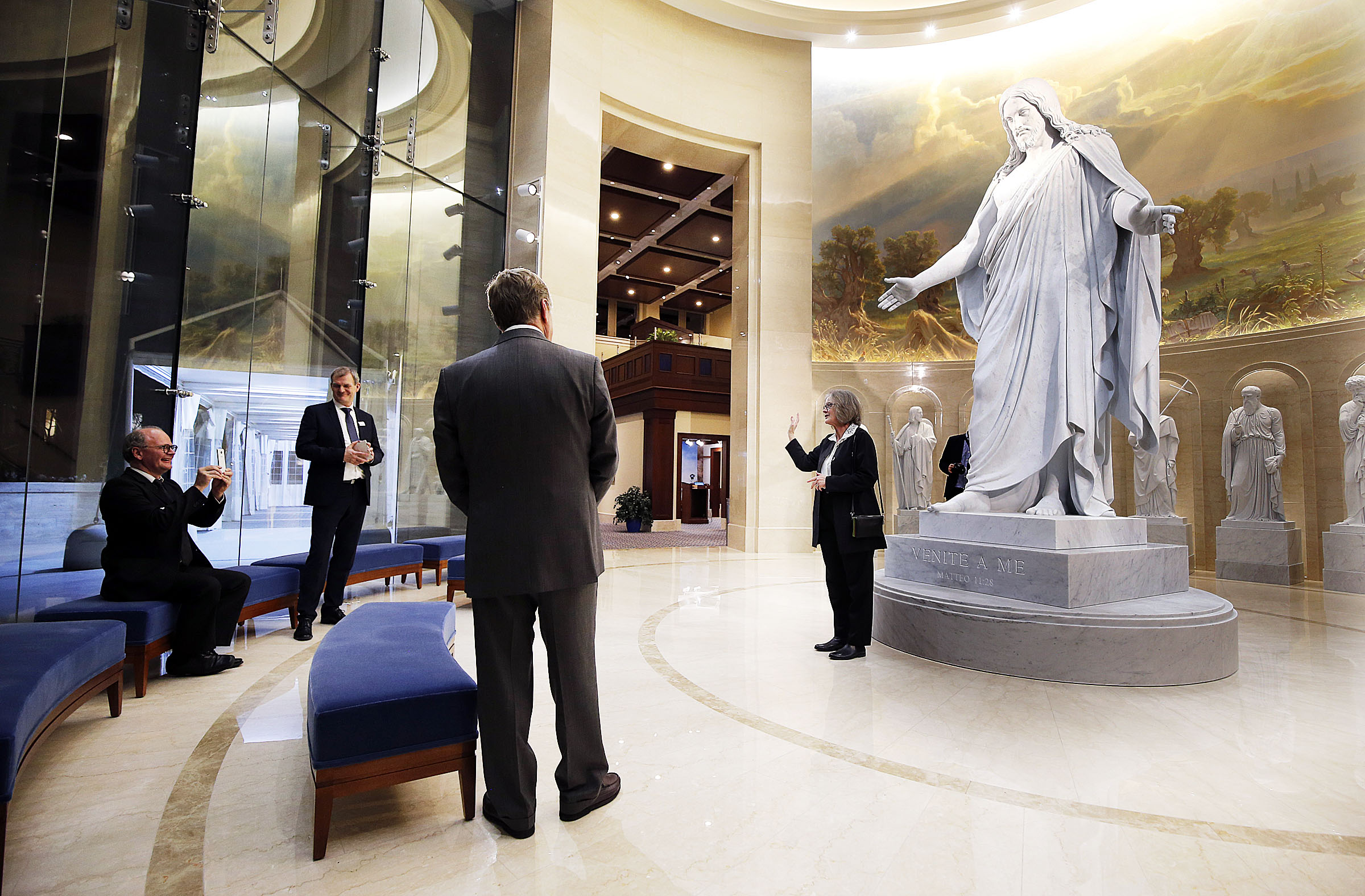 Bent Sloth, facility director at the Church of Our Lady in Copenhagen, Denmark, takes a photo of Susanne Torgard, curator at the church, which is home to Thorvaldsen's Christus statue, at the base of a digital, 3-D replica done in marble at the Rome Italy Temple on Wednesday, Jan. 16, 2019. In the background is Steffen Ringgaard Andresen, the church's vicar priest, and in the foreground is Niels Valentiner, architect of the Rome Italy Temple.