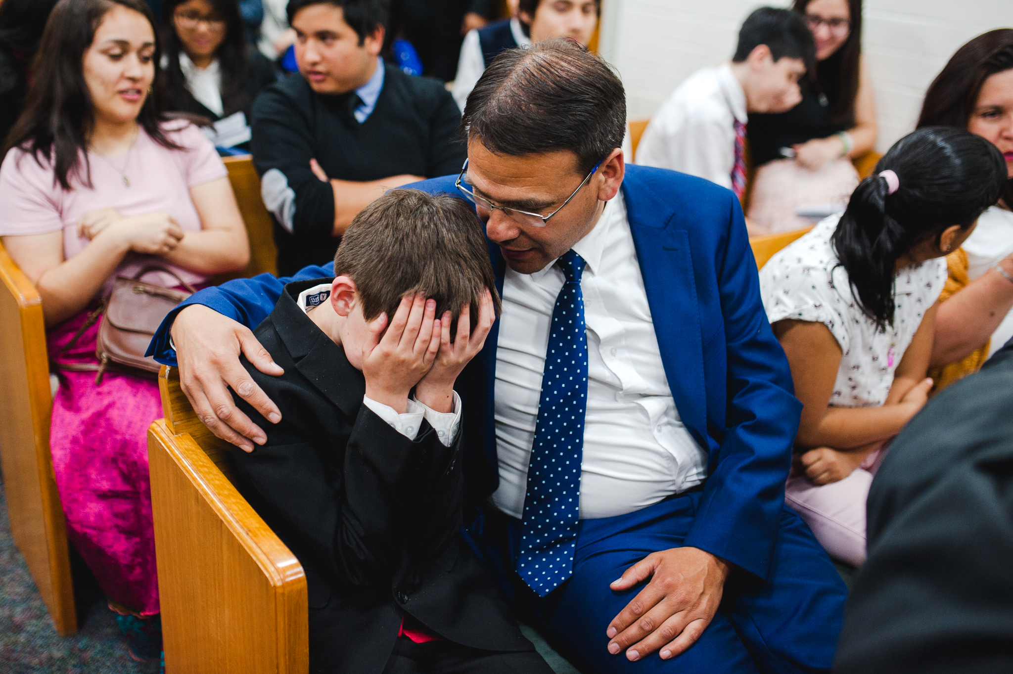 A young boy with his father at a devotional for youth in La Cisterna, Chile, on Nov. 9.