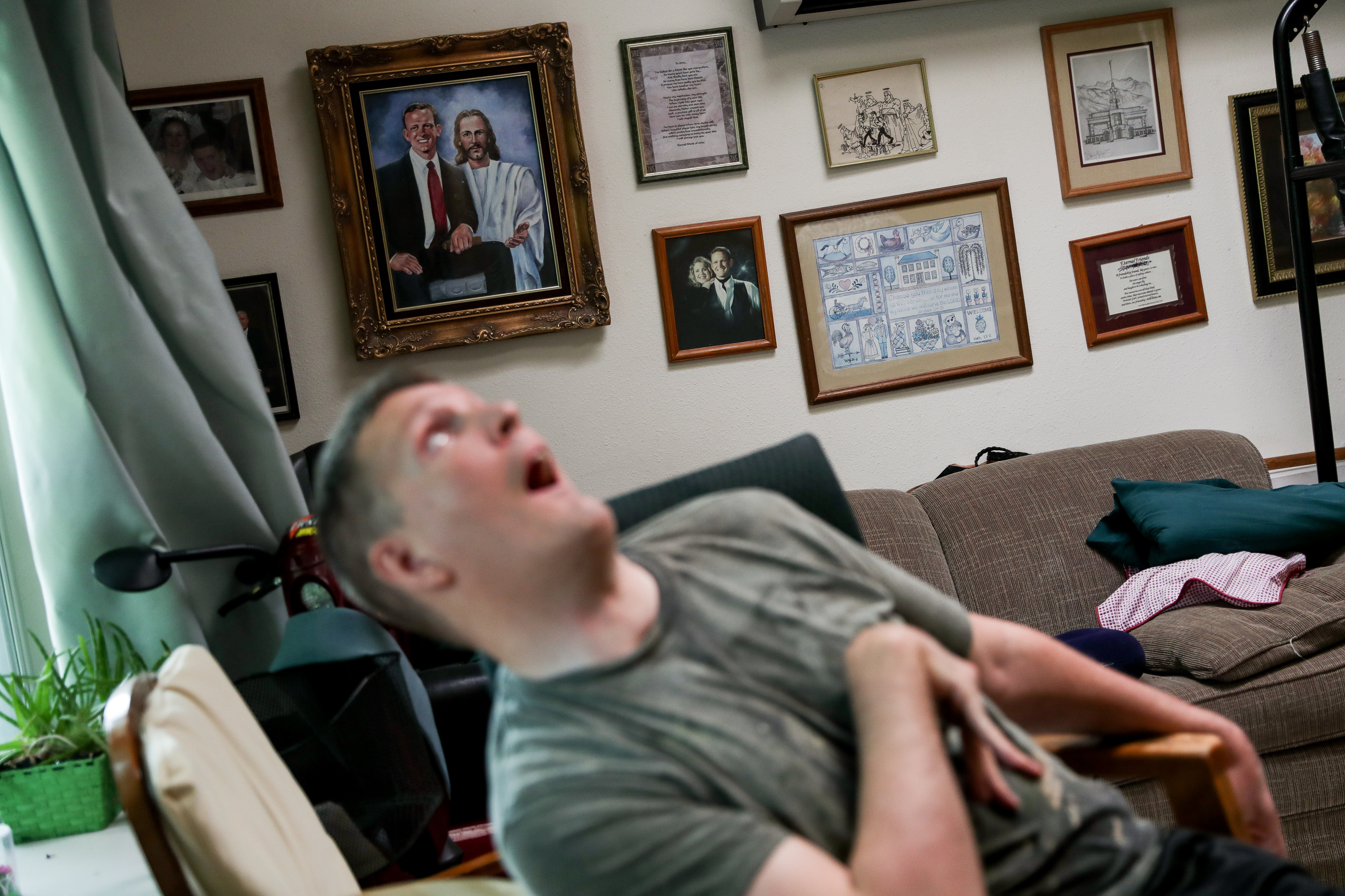 Orin Voorheis rolls around in a desk chair for physical therapy at his home in Pleasant Grove, Utah, on Tuesday, July 10, 2018.