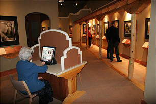 Museum docent Ruth Oborn familiarizes herself with the exhibit's video touch- screen feature.