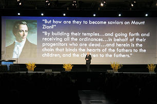 """Elder Neil L. Andersen speaks to youth of the obligation to be """"saviors on Mount Zion"""" as a quote from Joseph Smith is projected behind him."""