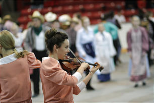 A fiddler plays for young people to do line dancing during the cultural program in Calgary's Stampede Corral.