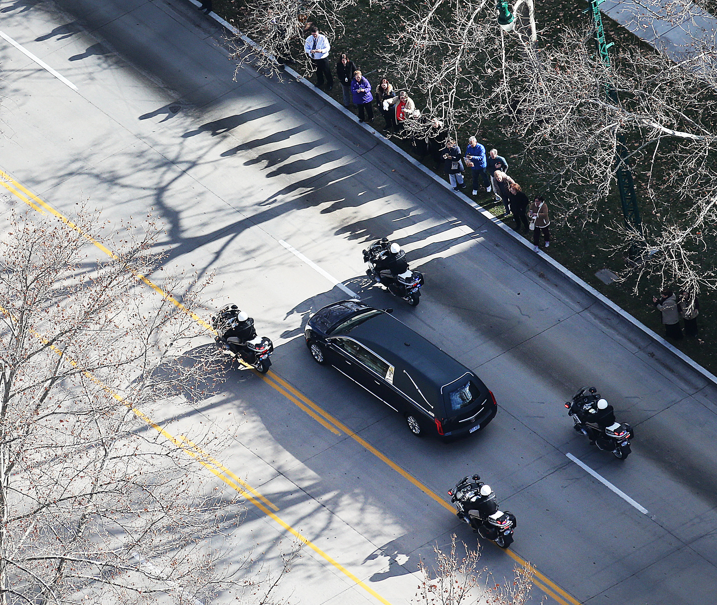 Mourners watch as the funeral procession for Church President Thomas S. Monson makes its way to the Salt Lake City cemetery on Friday, Jan. 12, 2018.