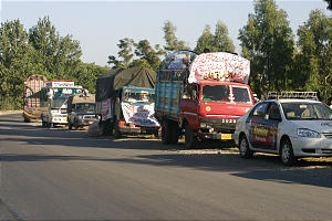 Church caravan, with signs stating Church's name, delivers aid to victims in disaster zone.