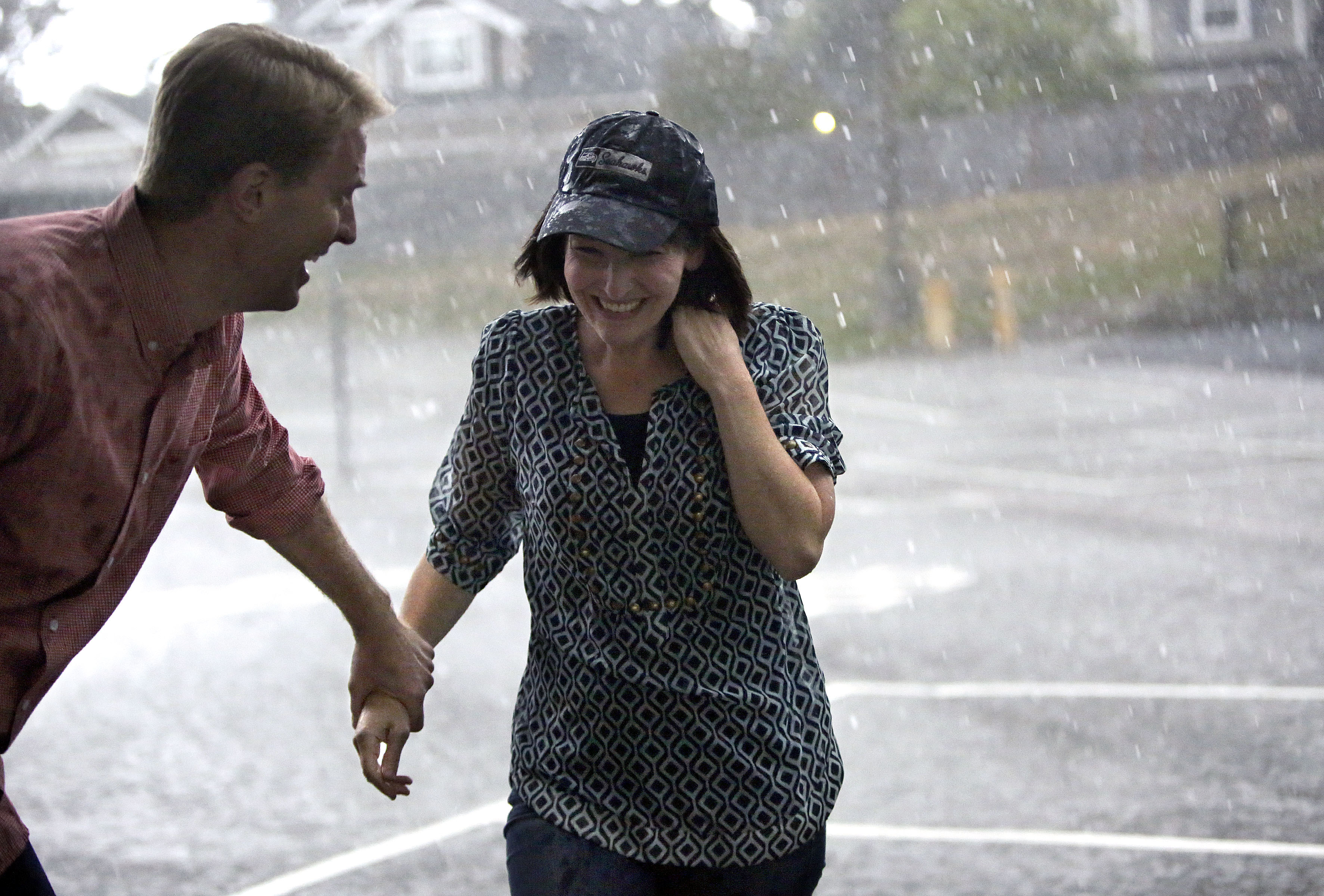Justin Allen pulls his wife Alexis Allen out of the rain near their home in Renton, Wash., on Friday, Sept. 14, 2018.
