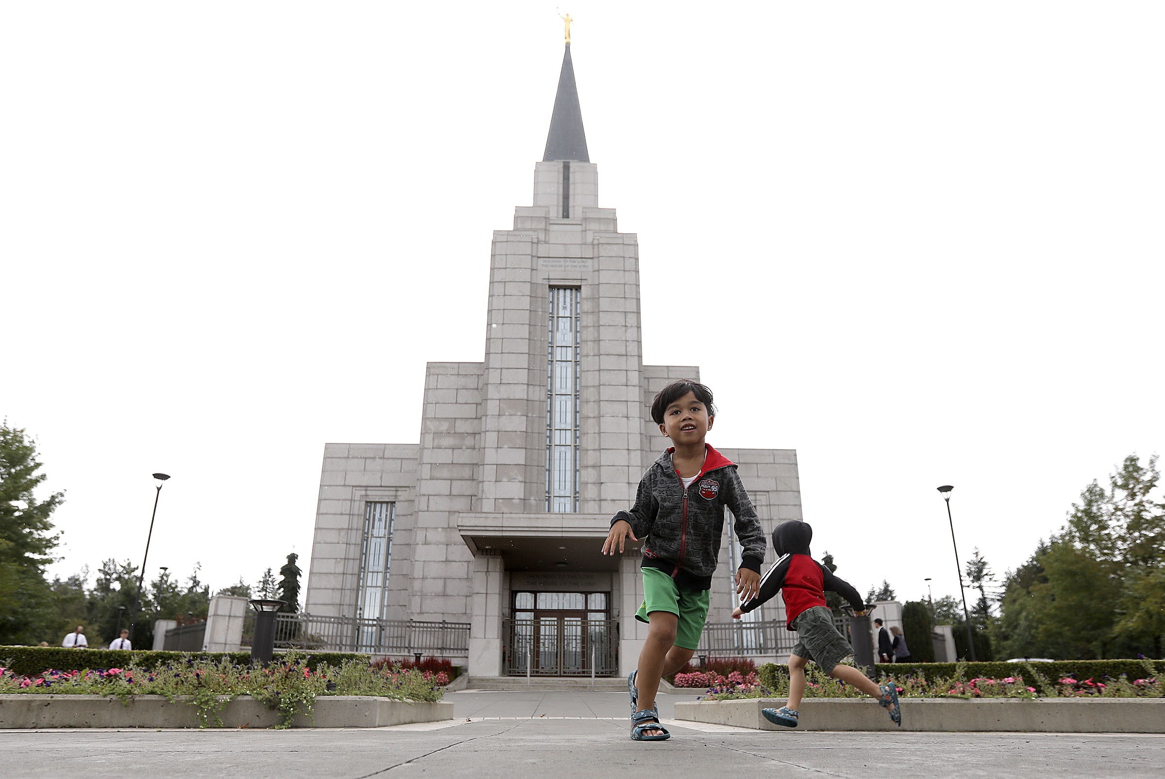 Hevenxen de Guzman and Baelfire de Guzman play in front of the Vancouver British Columbia Temple in Langley, British Columbia, on Sunday, Sept. 16, 2018.
