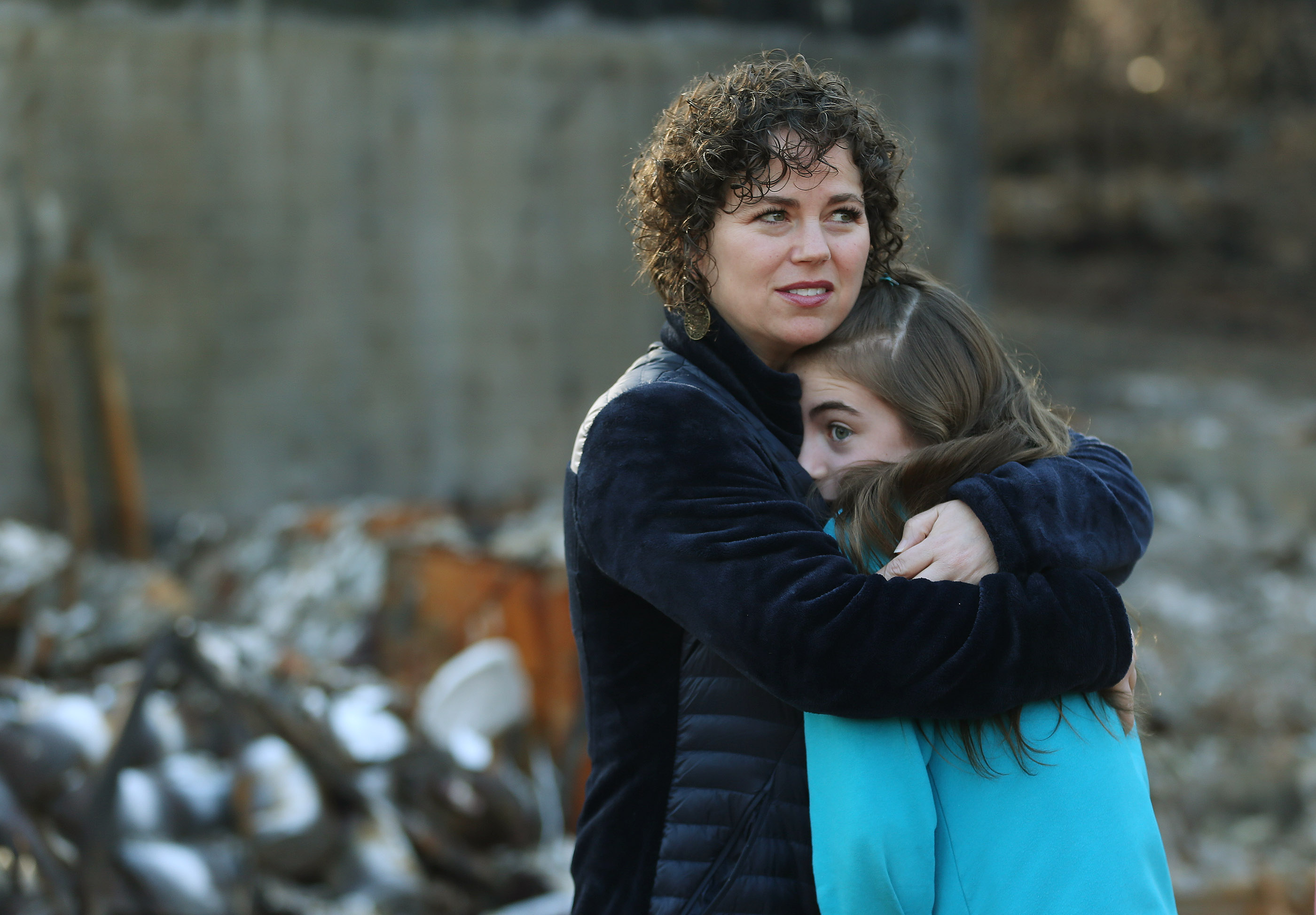 Brynn Chatfield holds her daughter Mckell as they survey their destroyed home in Paradise, California, on Saturday, Jan. 12, 2019, two months after the Camp Fire destroyed more than 18,000 homes and businesses.