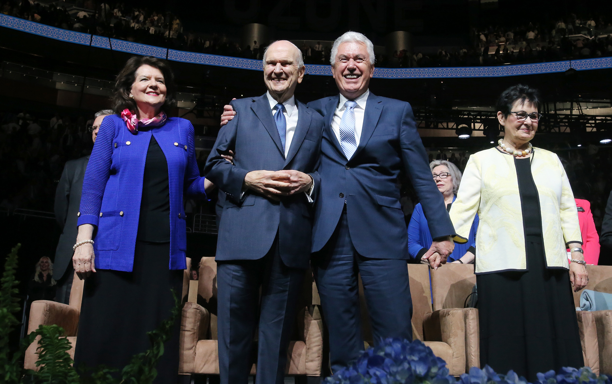 President Russell M. Nelson, is hugged by Elder Dieter F. Uchtdorf of the Quorum of the Twelve Apostles and they stand by the wives, Sister Wendy Nelson, left, and Sister Harriet Uchtdoft, right, following the June 9, 2019, devotional at the Amway Center in Orlando, Florida.